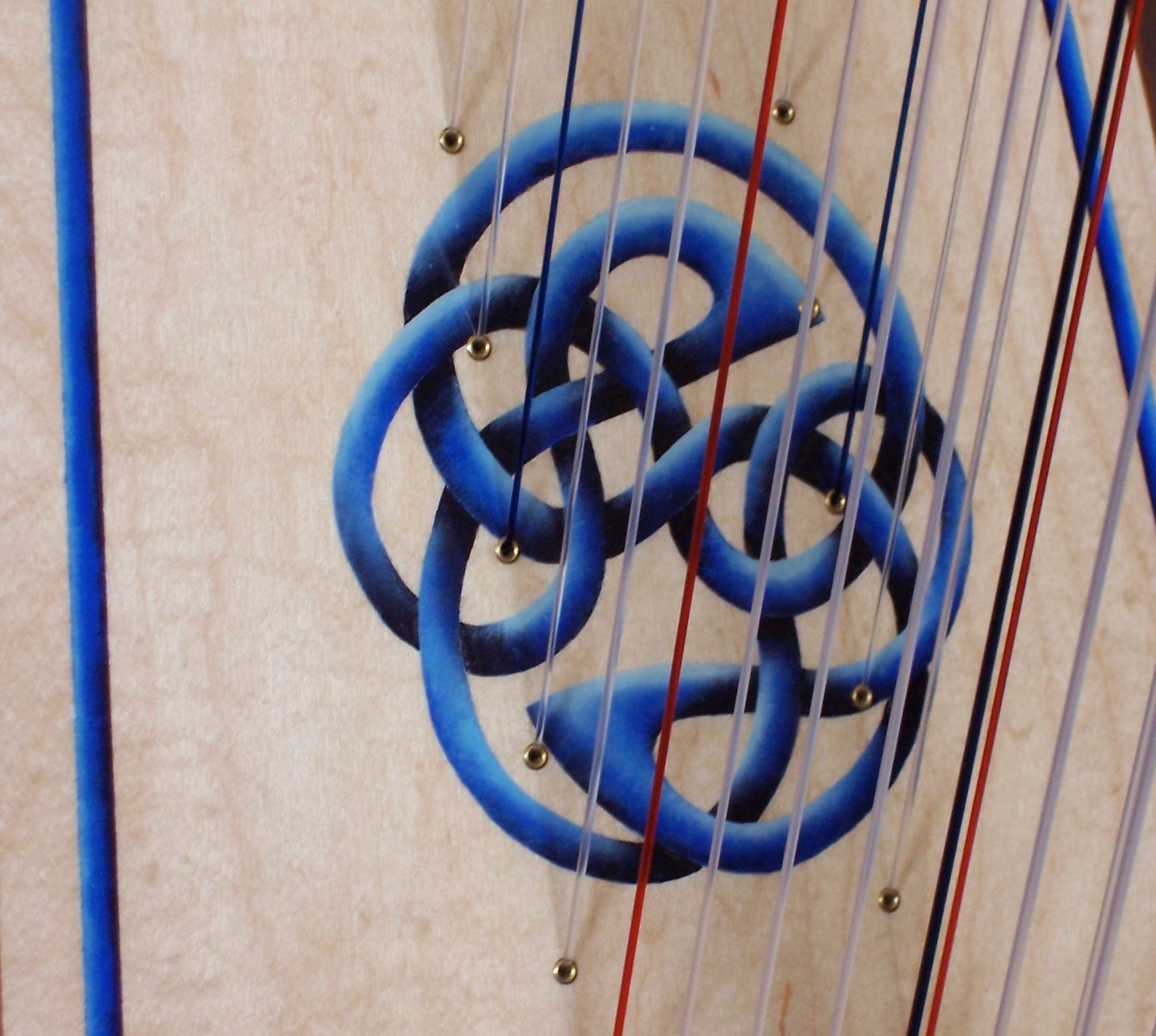 Close up of a double harp showing the two rows of strings with an optional hand painted Endless Knot.
