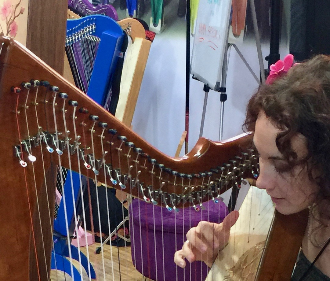 Camille Fournier at NAMM 2015 playing a Rees Mariposa Concert Line Harp tuned in E-flat Major.