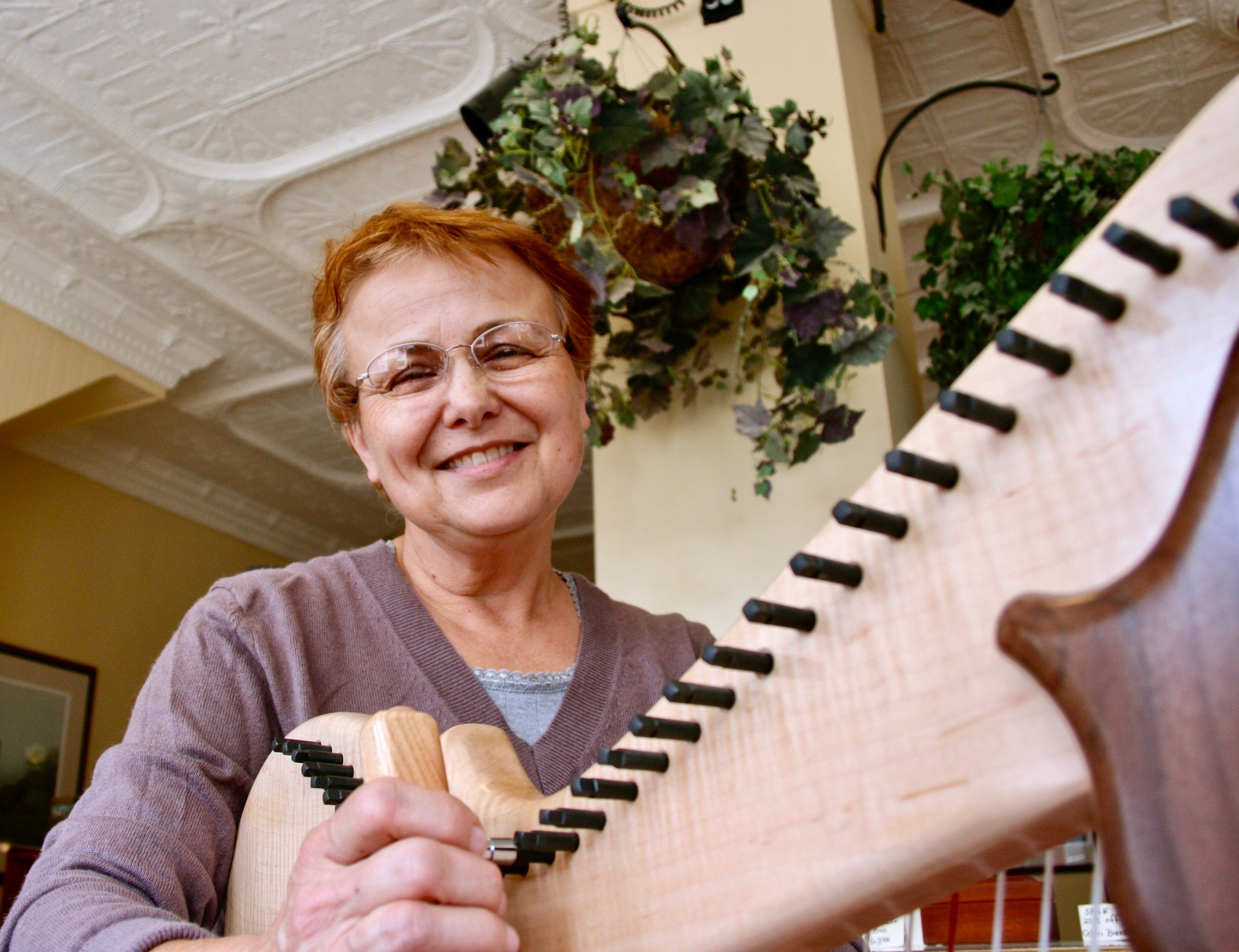 Joann Irwin tuning a harp (again) before she packs it to ship out.