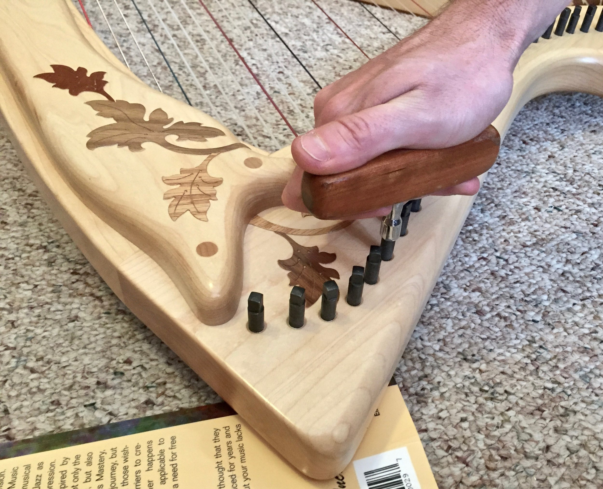 Lay your harp, string side down, with the point on a book and then firmly press the loose pin back in with your tuning wrench.