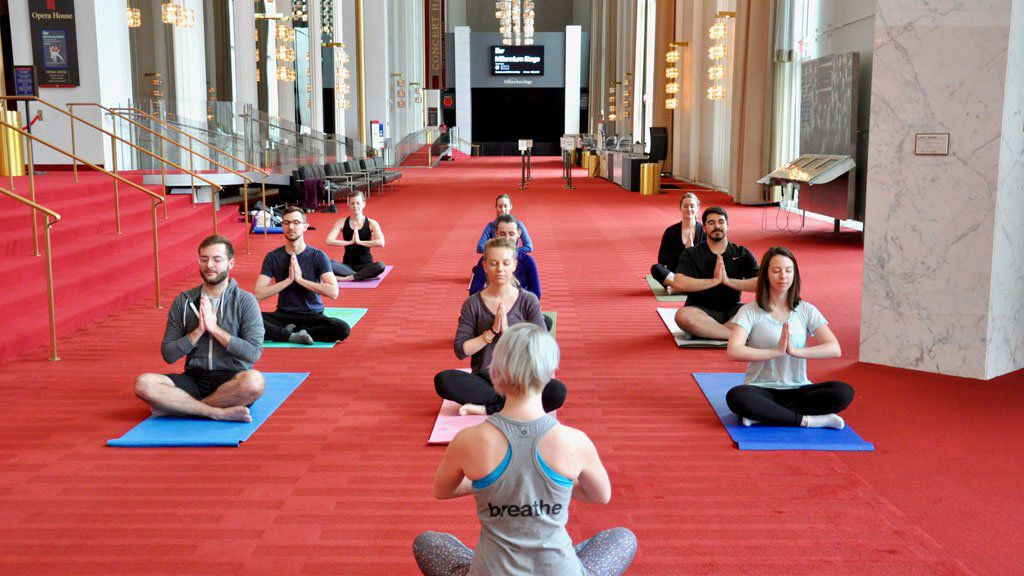 Kelly Carnes instructs Kennedy Center staff in the Grand Foyer in preparation for the free community yoga program, part of the Sound Health Initiative. Credit: Monica Holt