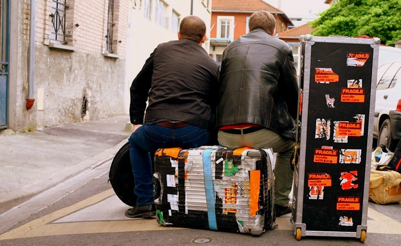 musicians sitting on luggage.jpg