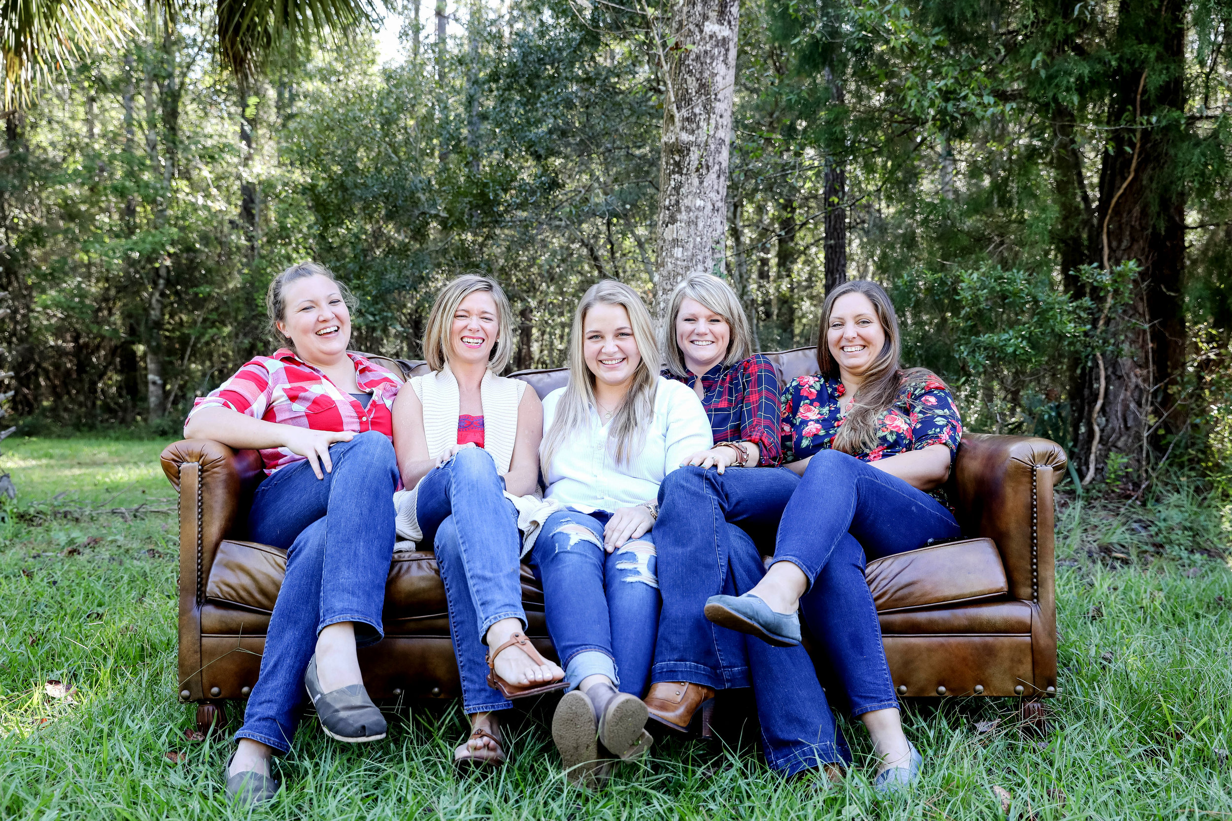 The girls of Southern Priss sit on a couch and laugh together in a field.