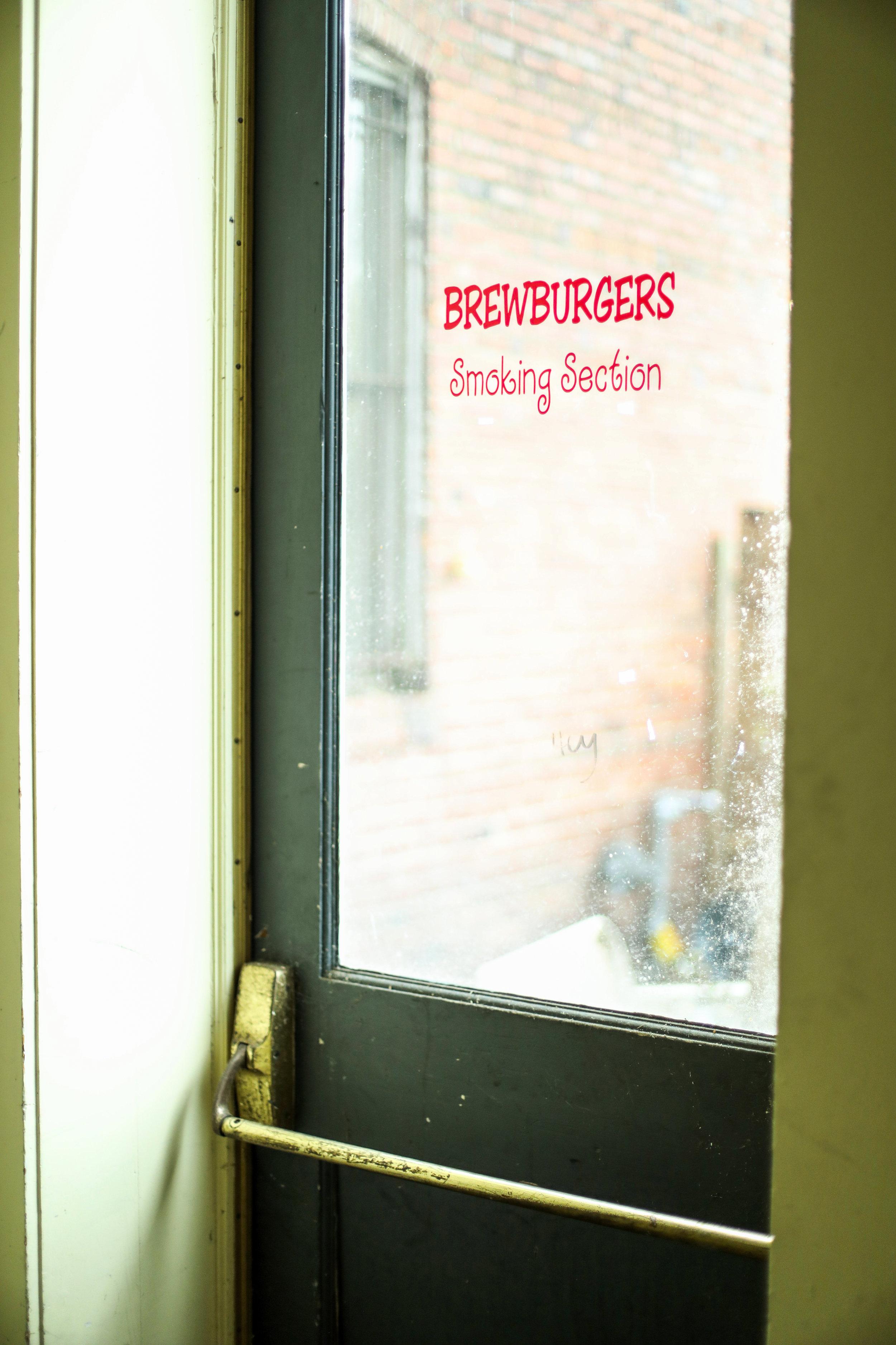 "a push door with a ""brewburger's smoking section"" sign"