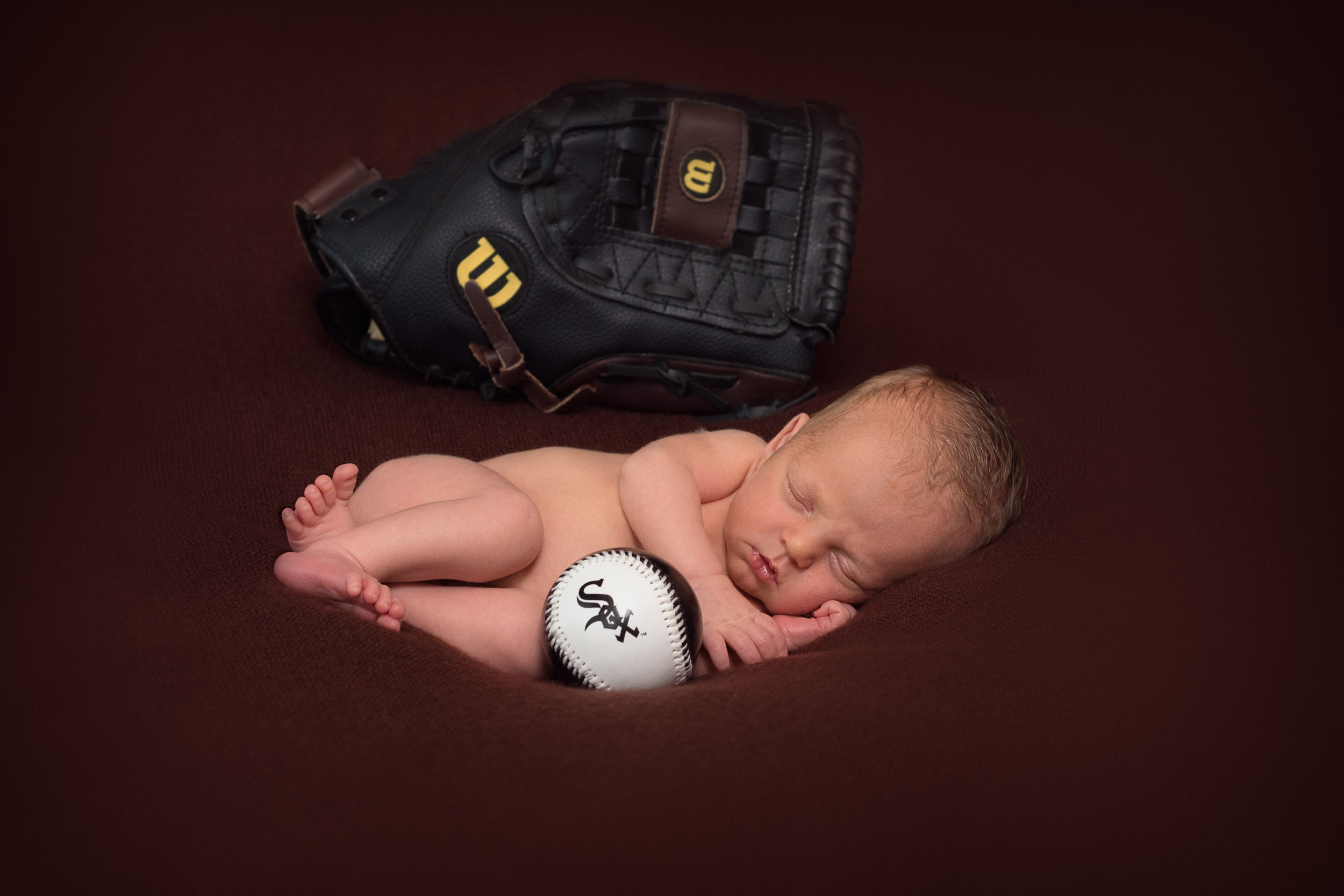 newborn baby with a ball and baseball glove.jpg