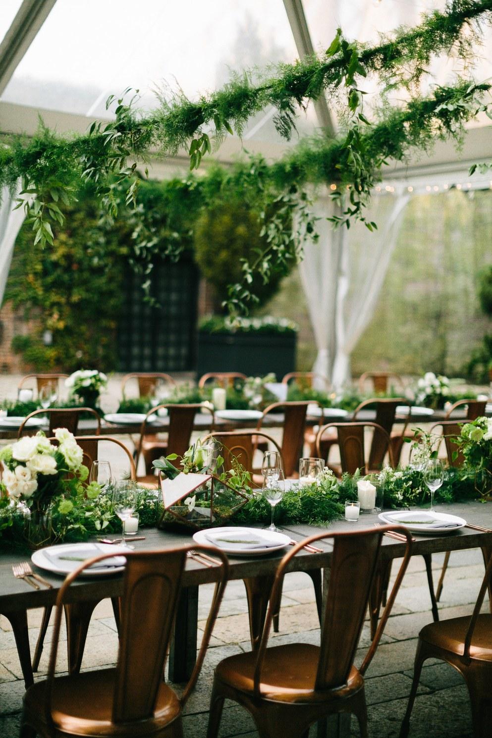 Greenery garlands in a transparent wedding tent. Photo by Chaz Cruz via Brides.com