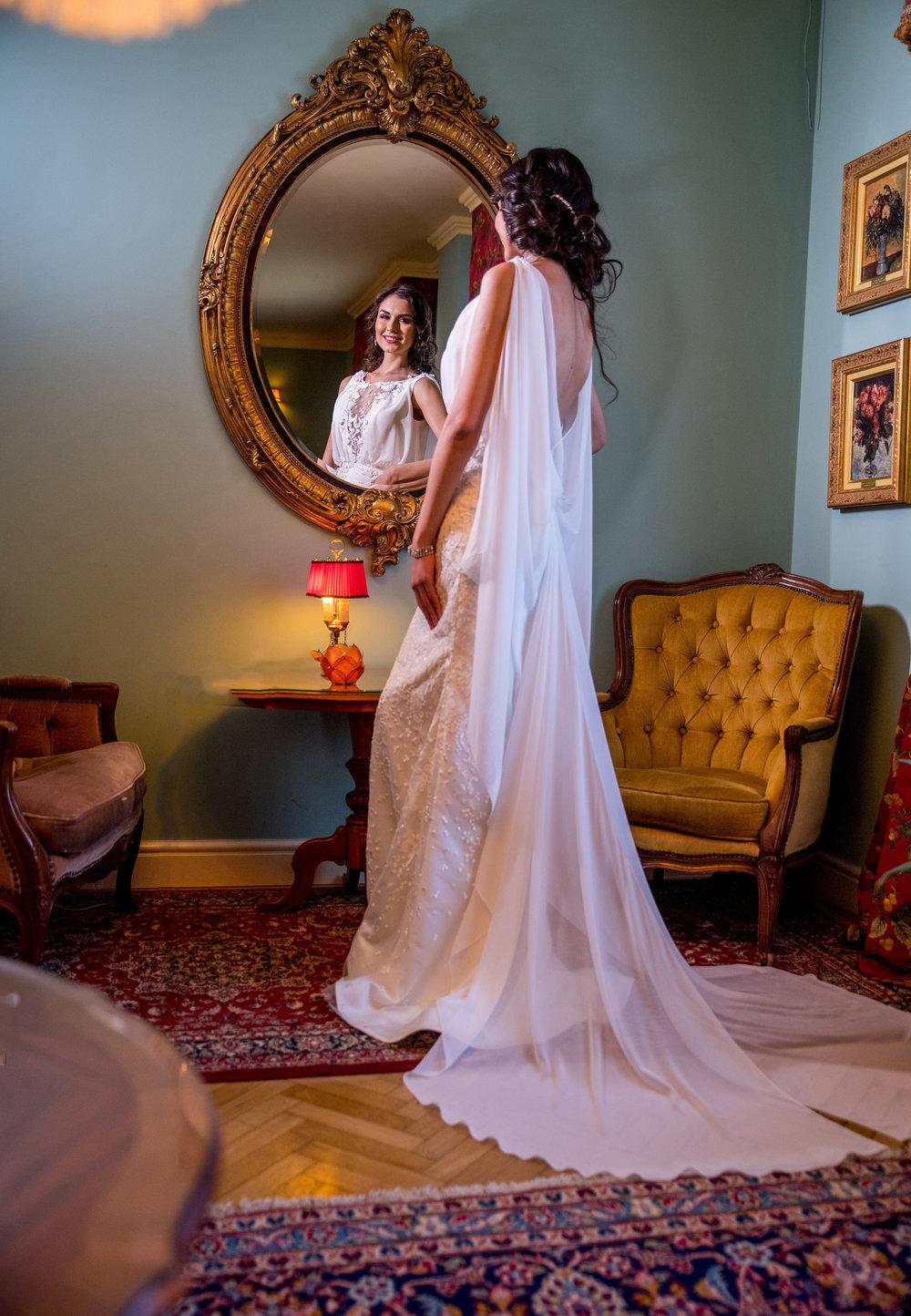 Featured:  Aster , backless wedding dress featuring a superb, light cape.