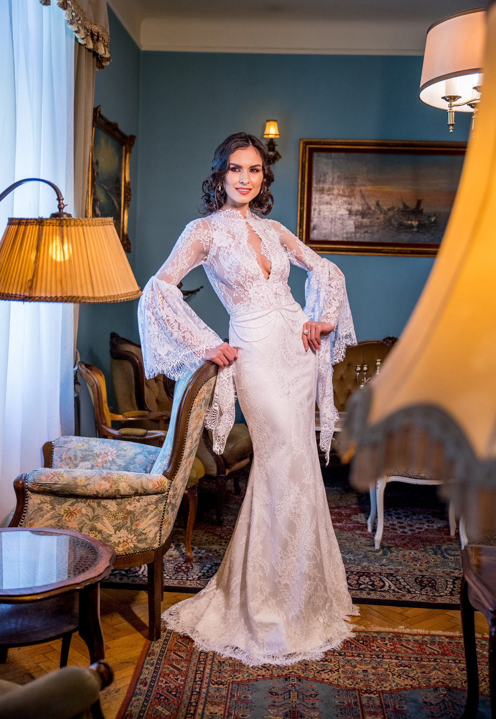 Featured:  Acacia , ivory lace wedding dress with long bell sleeves and waist accessorized with pearls