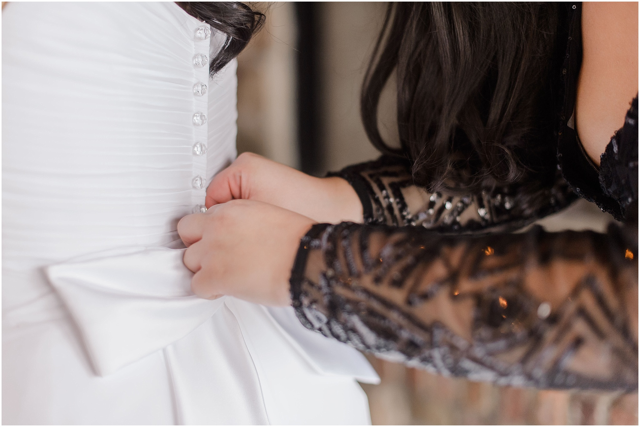 bride getting the dress buttoned by her best friend