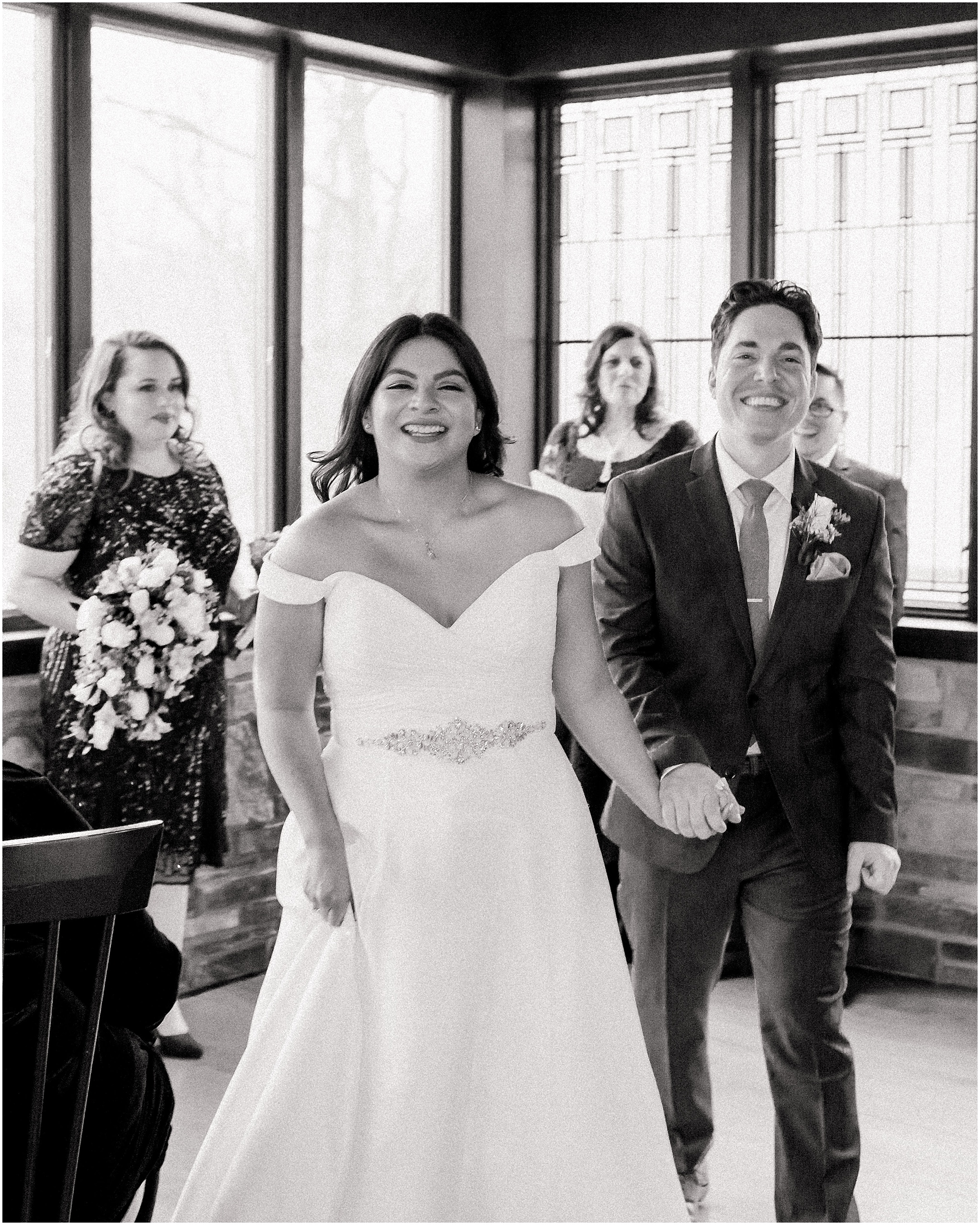 the newly married bride and groom walk up the aisle, happy, smiling and excited for their elopement