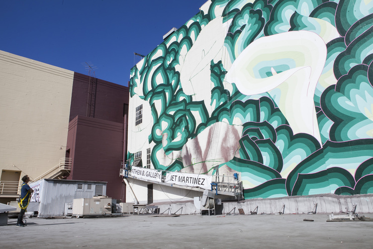 """Image of Jet Martinez in 2016 when working on his downtown Oakland mural, """""""" There's More to Green than Money."""" Source:    Amadeus Magazine"""