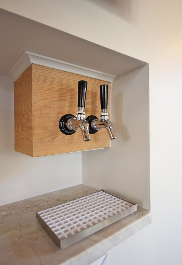 Custom-built beer taps. A keg fridge is located behind the wall in the under stair space.