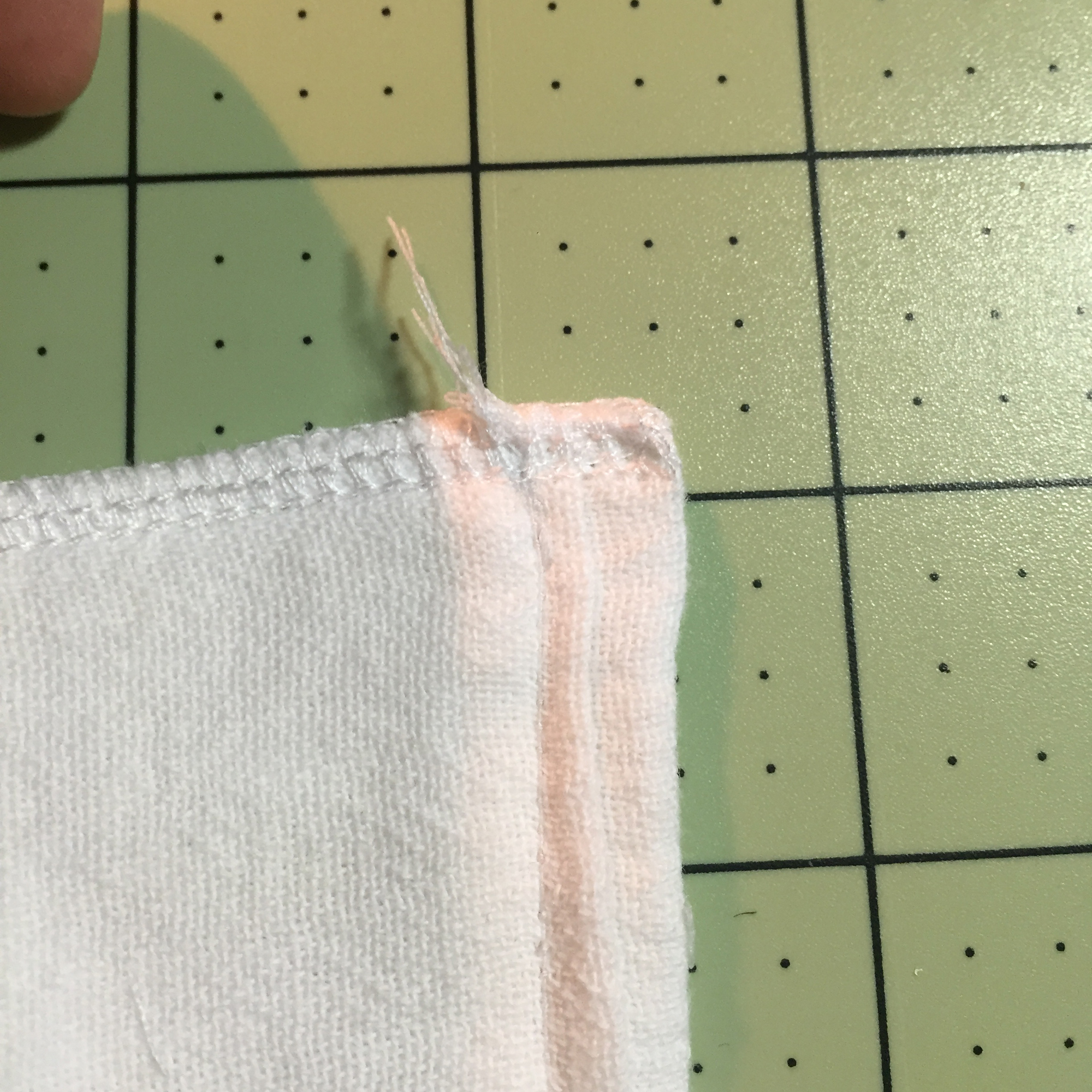 Once you pull through, the tail will be caught and safe in the serged stitches. Cut the extra tail.