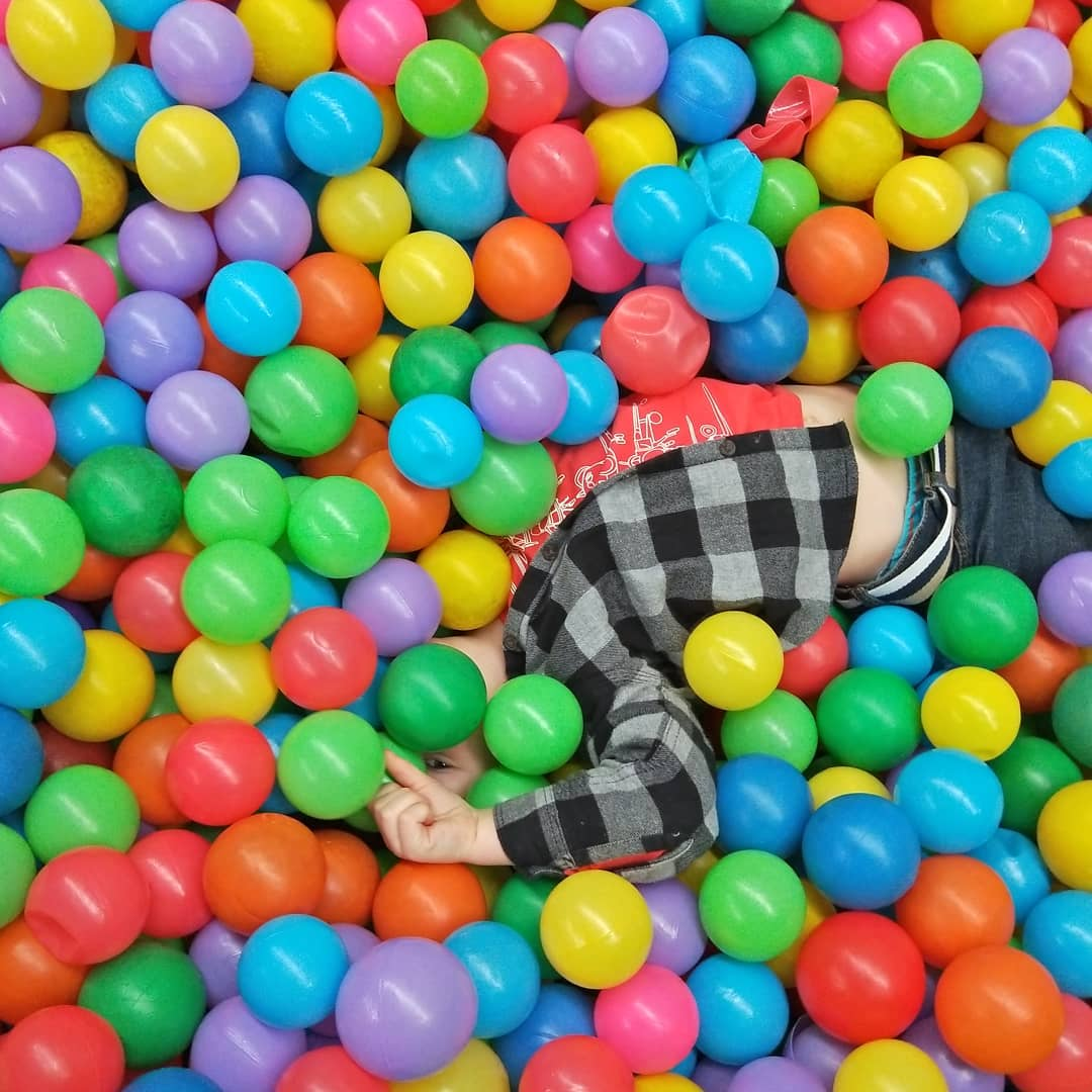 child-playing-in-brightly-coloured-ballpit