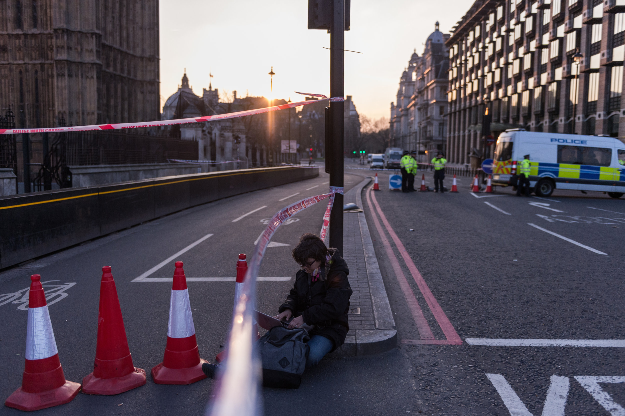 A journalist works under the police cordon surrounding Parliament Square after the incident.