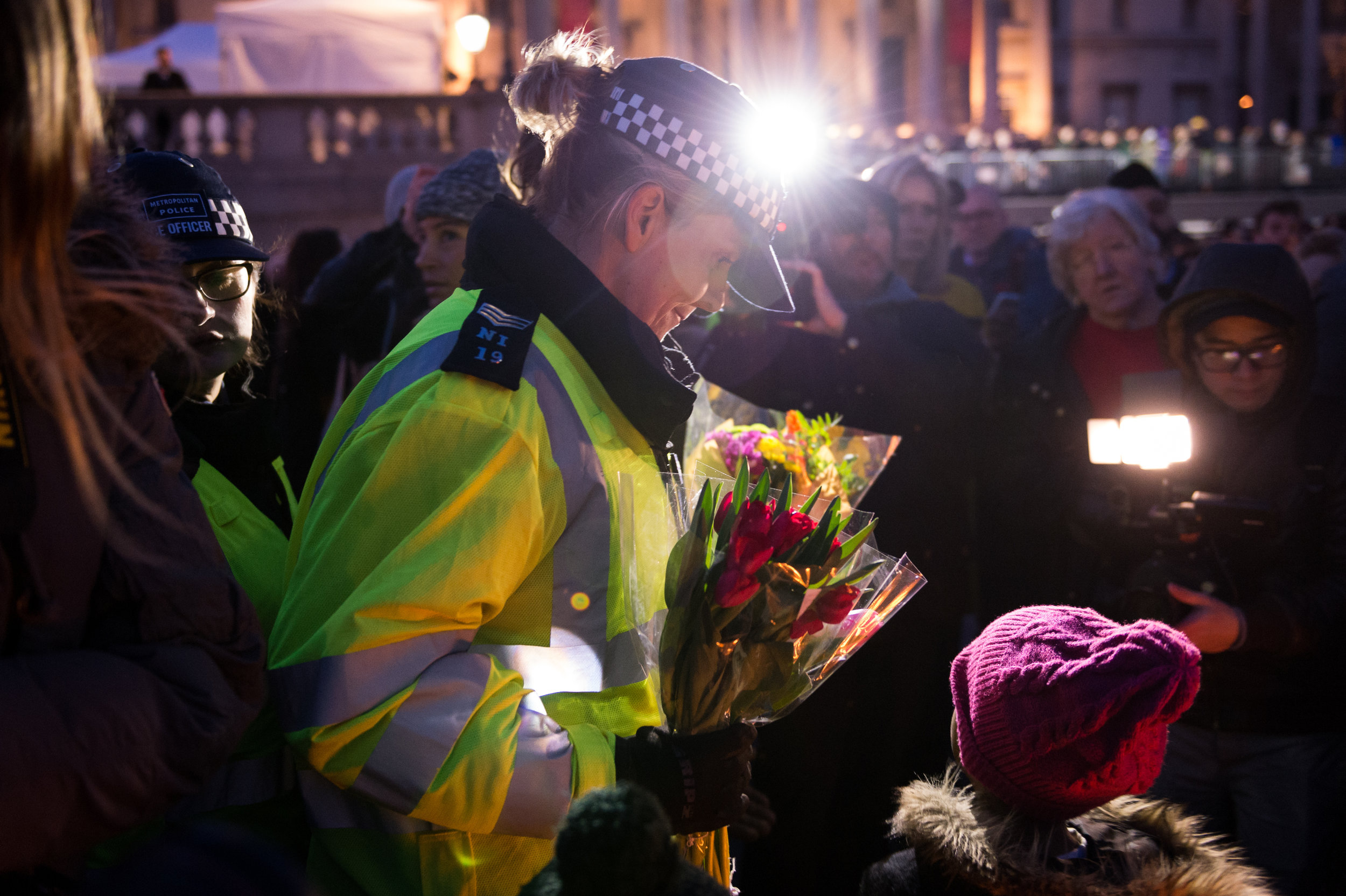 A police officer lays a floral tribute.