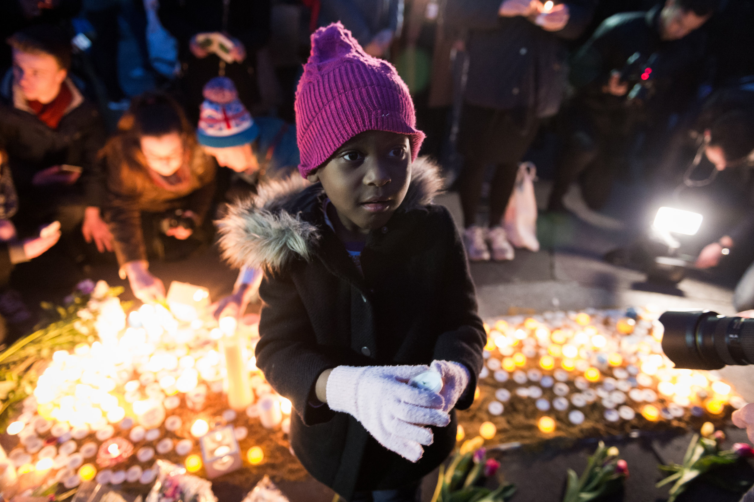 A young girl beckons her father to help light a candle in memory of those who lost their lives in the terror attack.