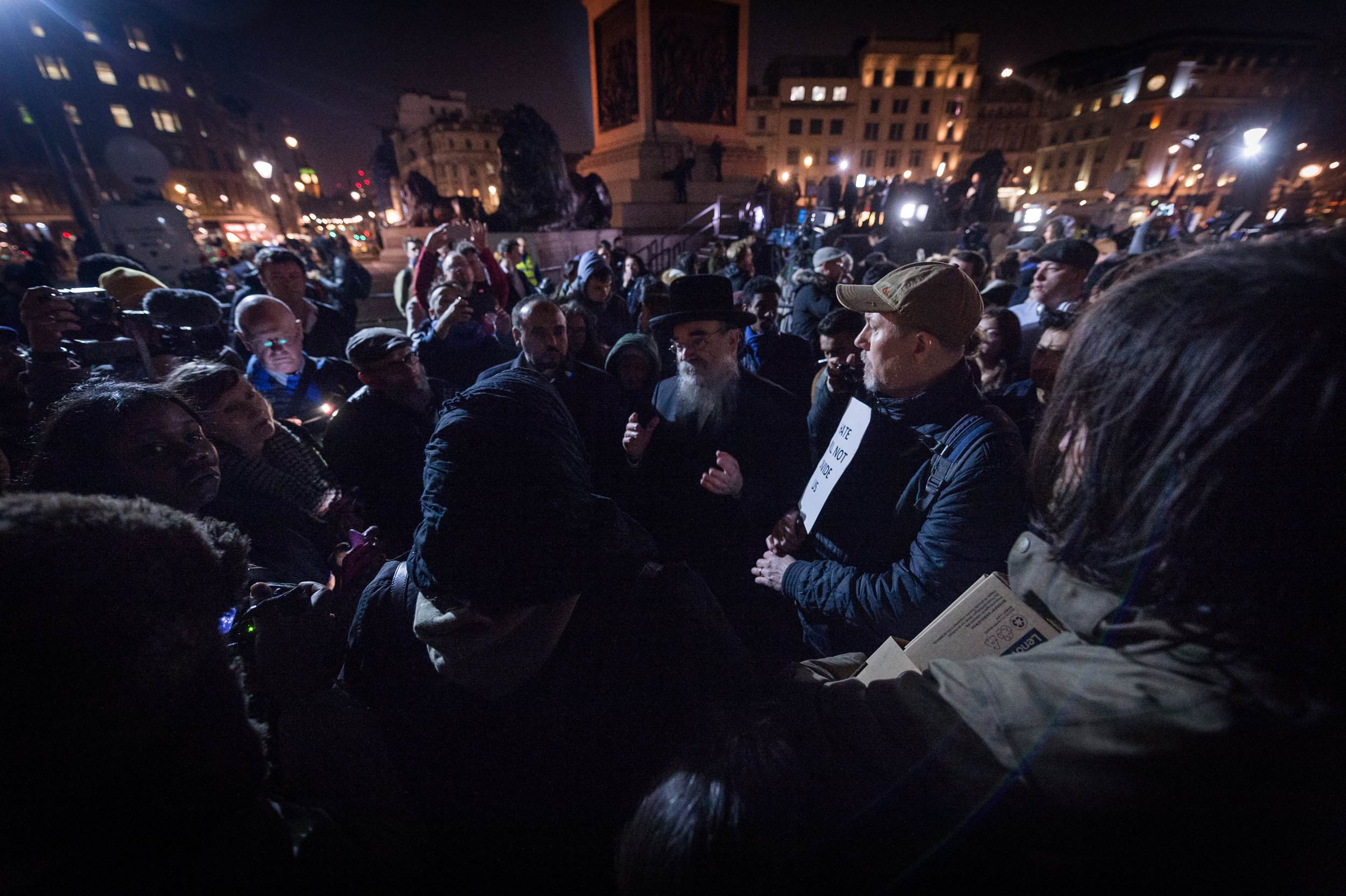 Crowds gather around a Rabbi and a Muslim woman as they engage in a public debate about how representatives of each religion can move forward from this tragedy.