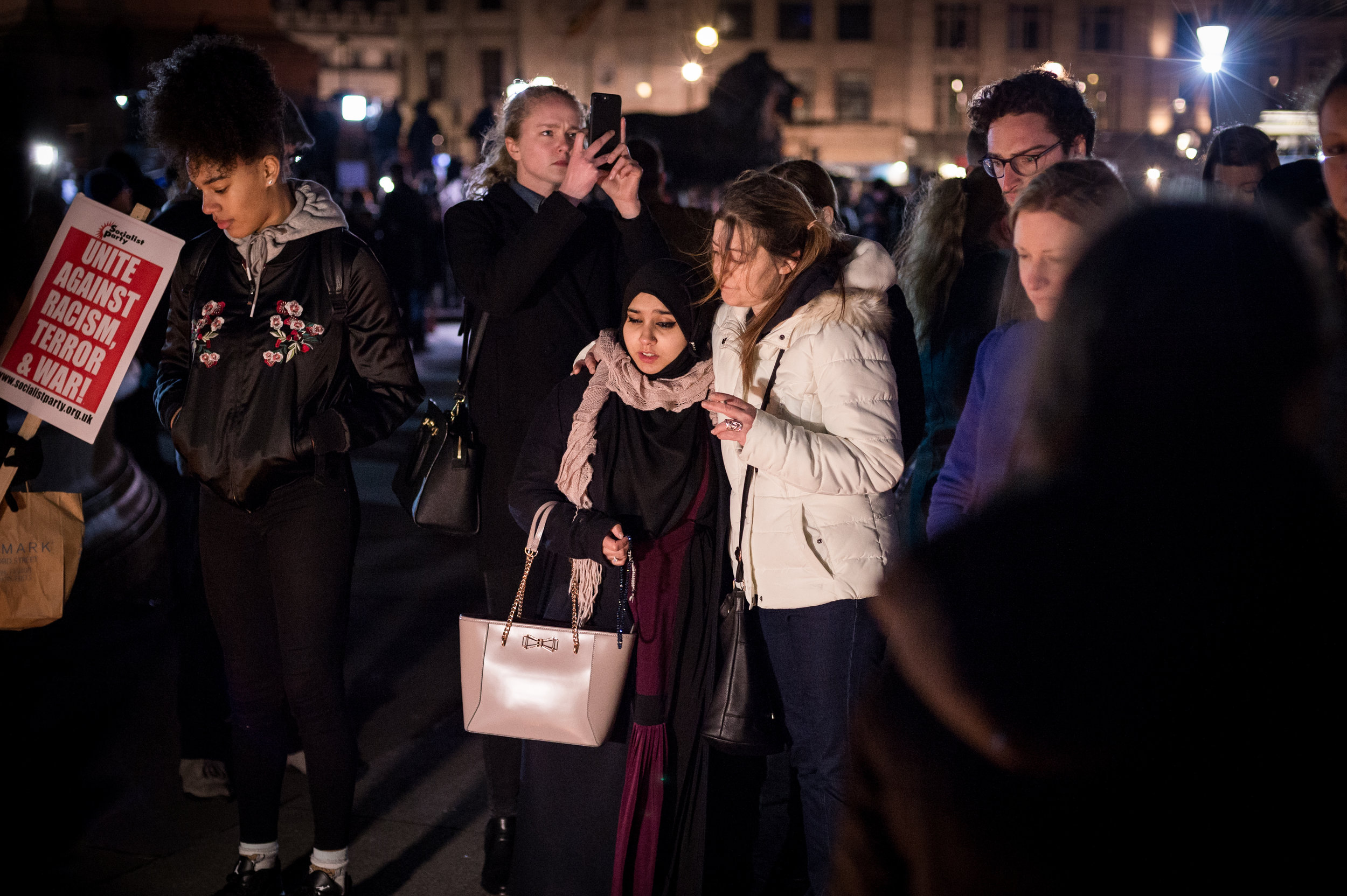 A visibly distressed Muslim woman is comforted by a friend.