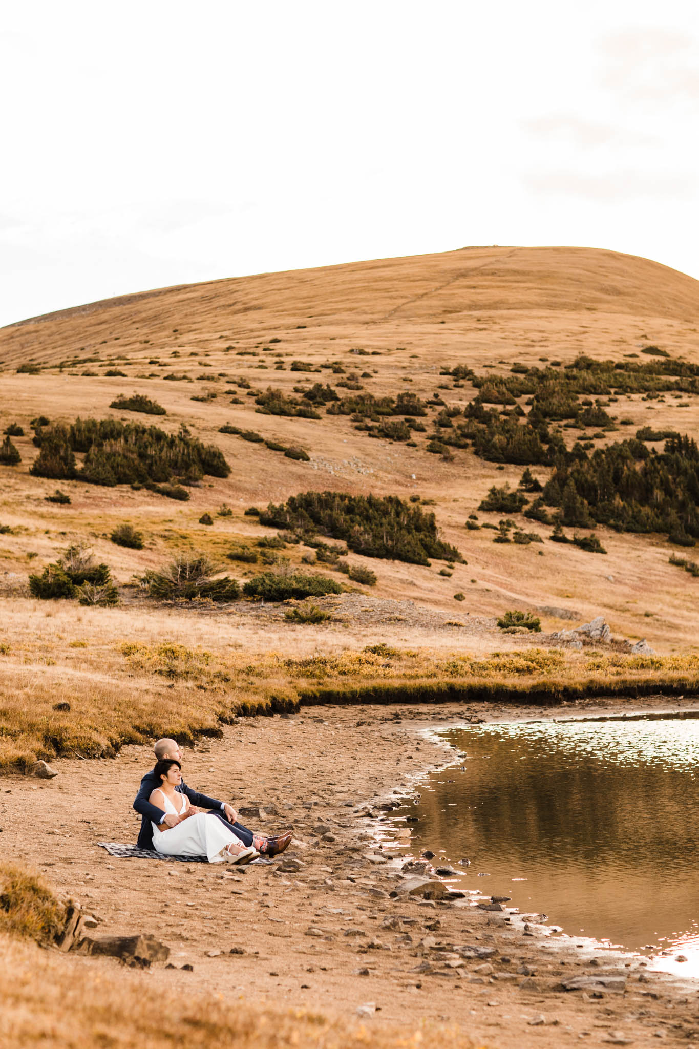 couple lounging by a mountain lake in Colorado | Rocky Mountain adventure session | Best Colorado elopement photographers