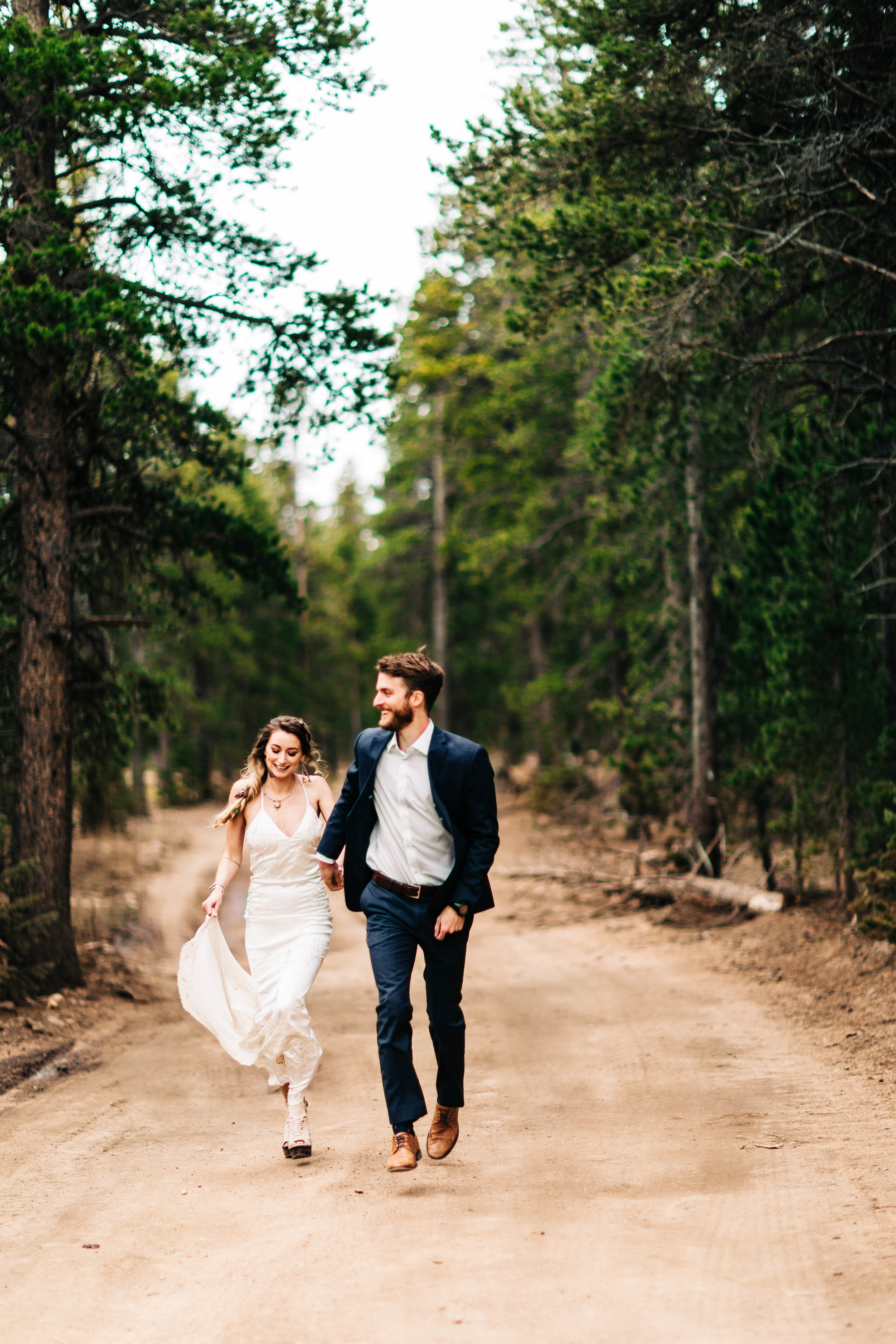Colorado couple running through the mountains on their elopement day | Rocky Mountain elopement photography