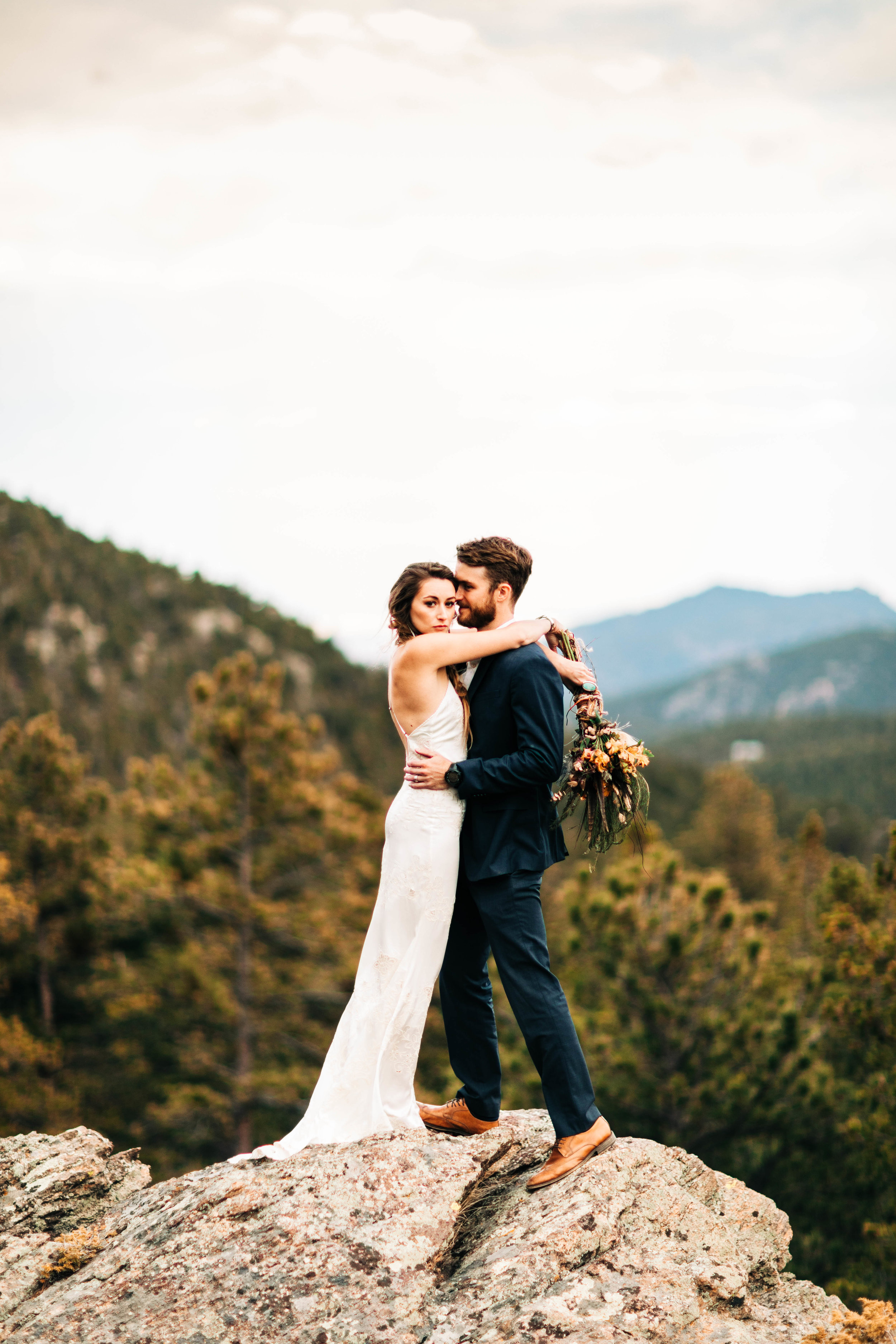eloping couple embracing on a cliff in the Rocky Mountains of Colorado