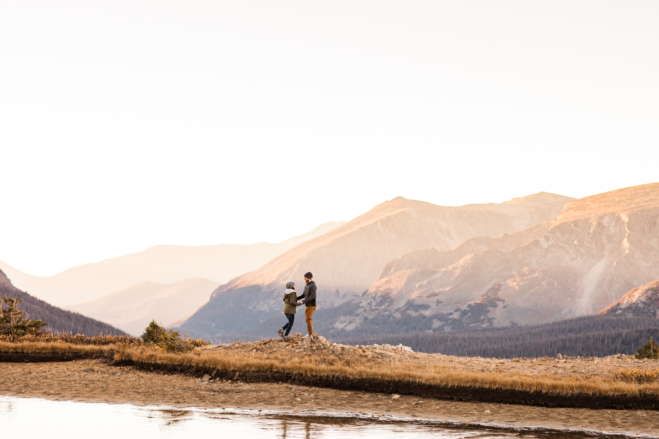 engaged couple walking by an alpine lake in the mountains | Colorado mountain elopement photographers