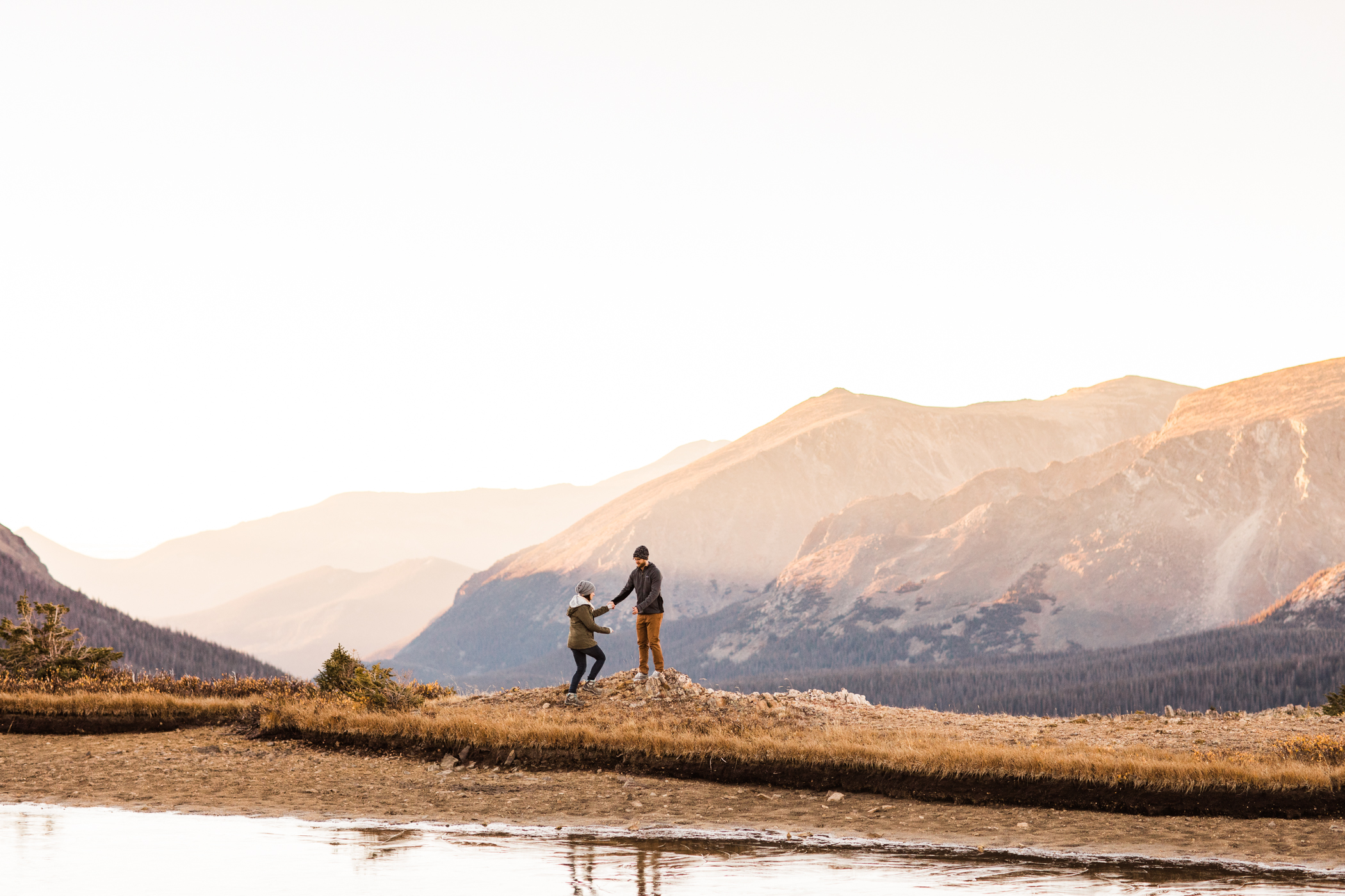 engaged couple walking by an alpine lake in the mountains | Rocky Mountain elopement photographers