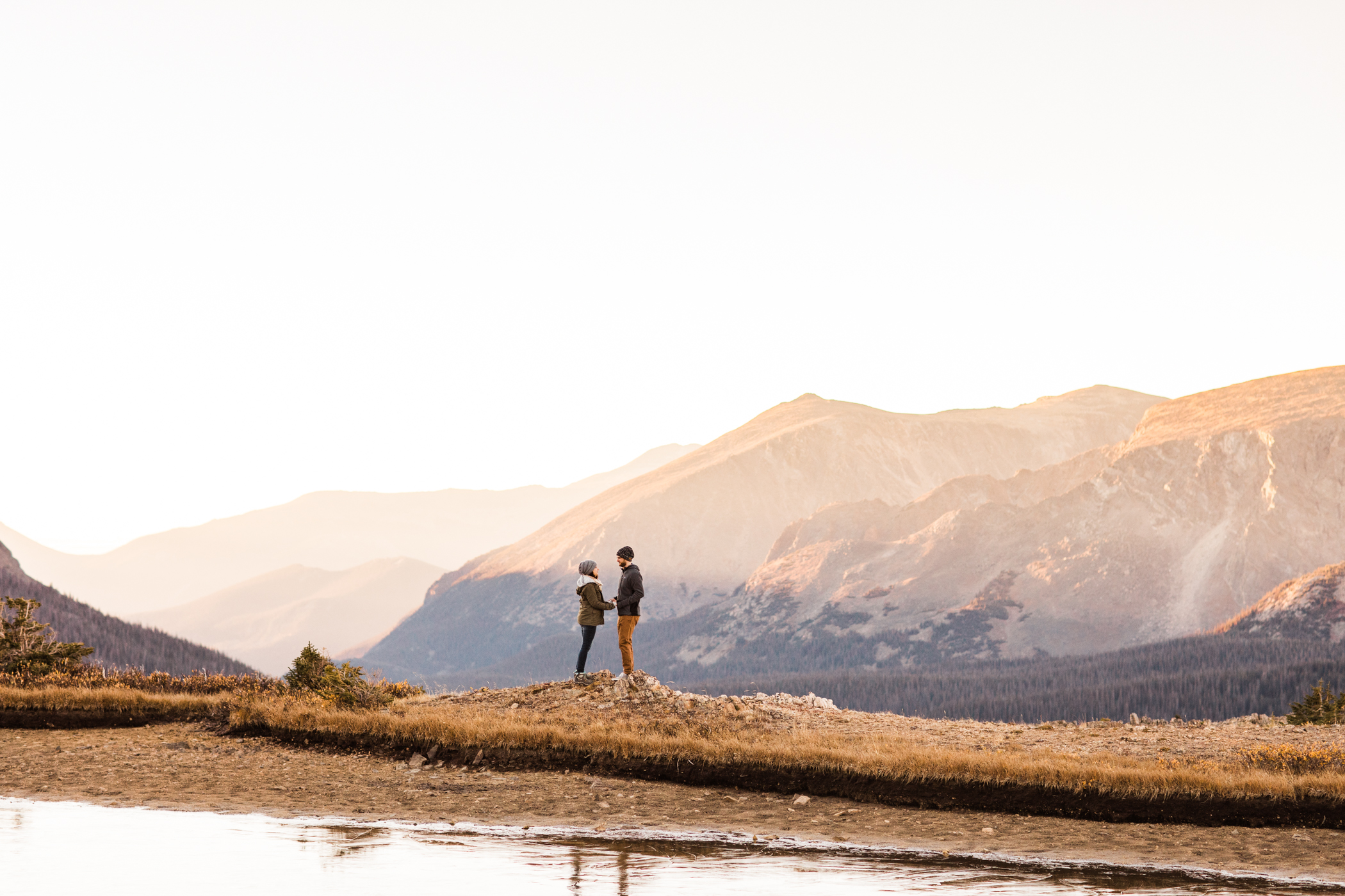 adventurous couple walking by an alpine lake in the mountains | Rocky Mountain elopement photographers