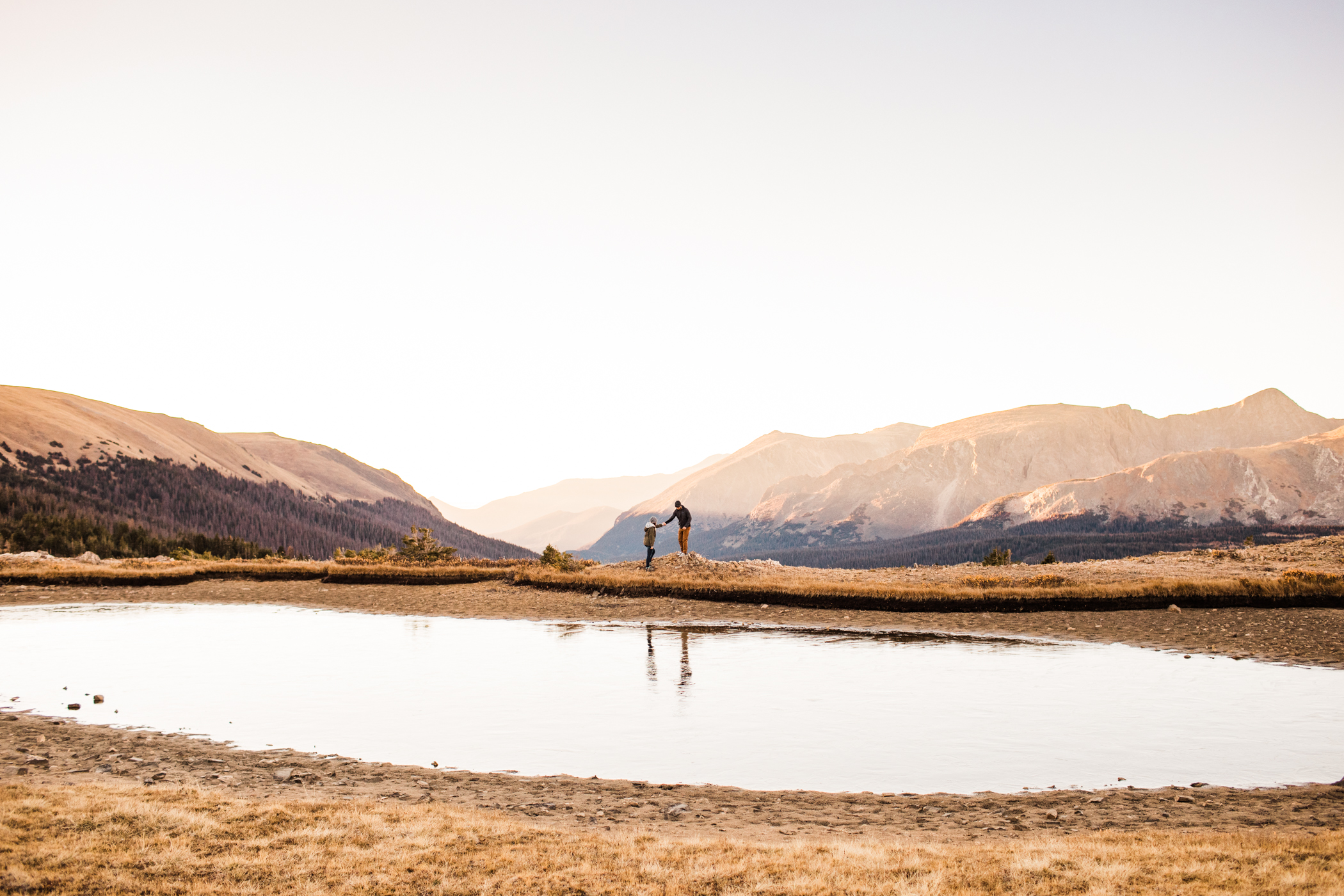 adventurous couple walking by an alpine lake in the mountains | Colorado elopement photographers