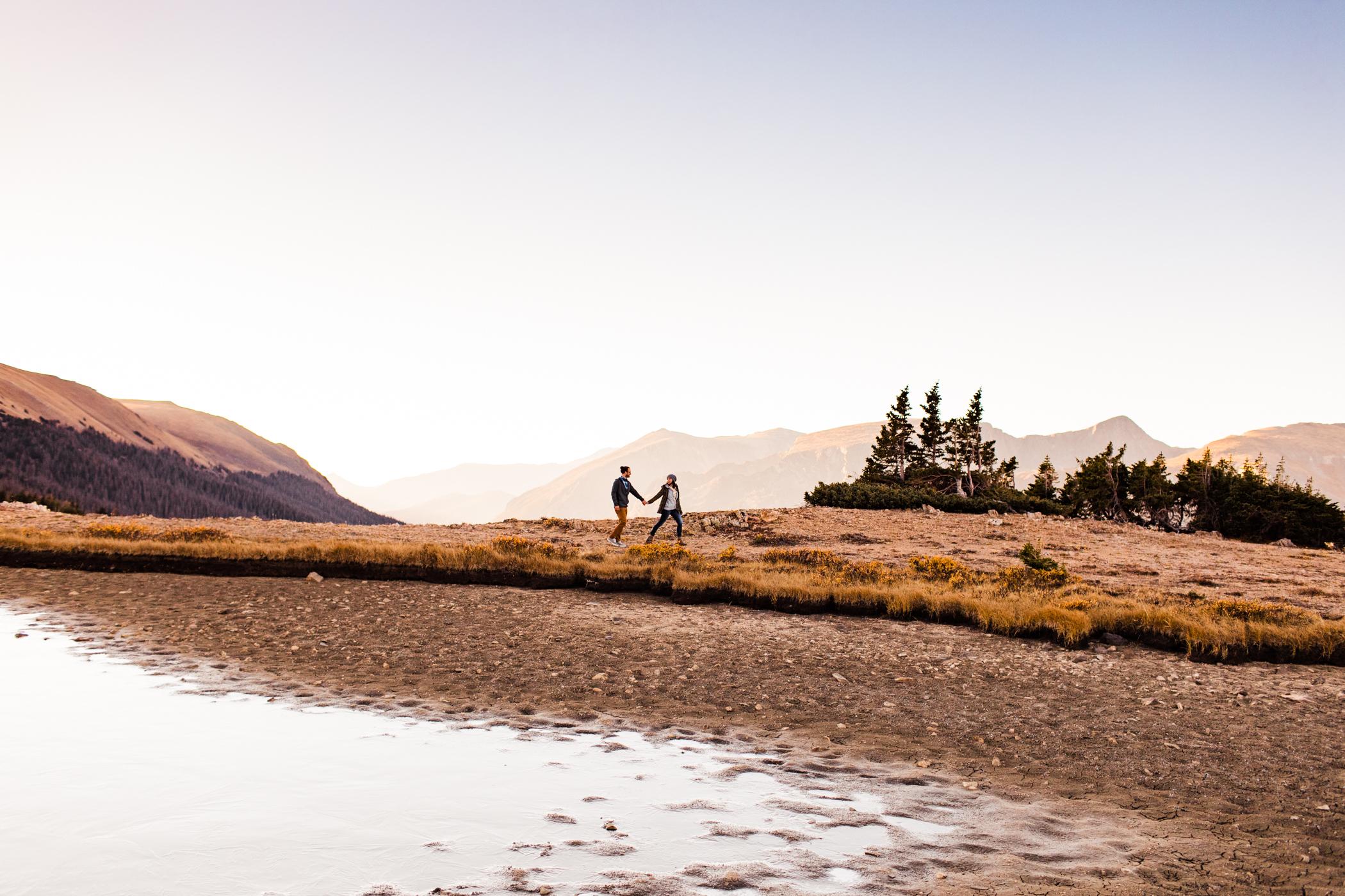 engaged couple wandering through the alpine tundra in Rocky Mountain National Park | Colorado adventure wedding photographers