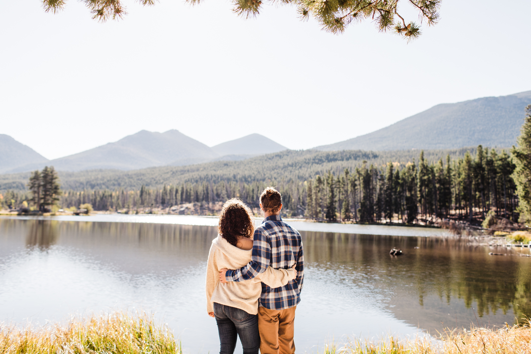 engaged couple looking out at Sprague Lake in Colorado | Rocky Mountain elopement photographers