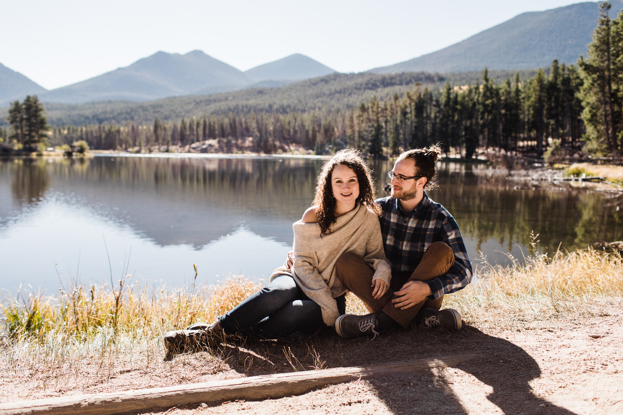 engaged couple sitting by Sprague Lake in Colorado | best Rocky Mountain elopement photographers