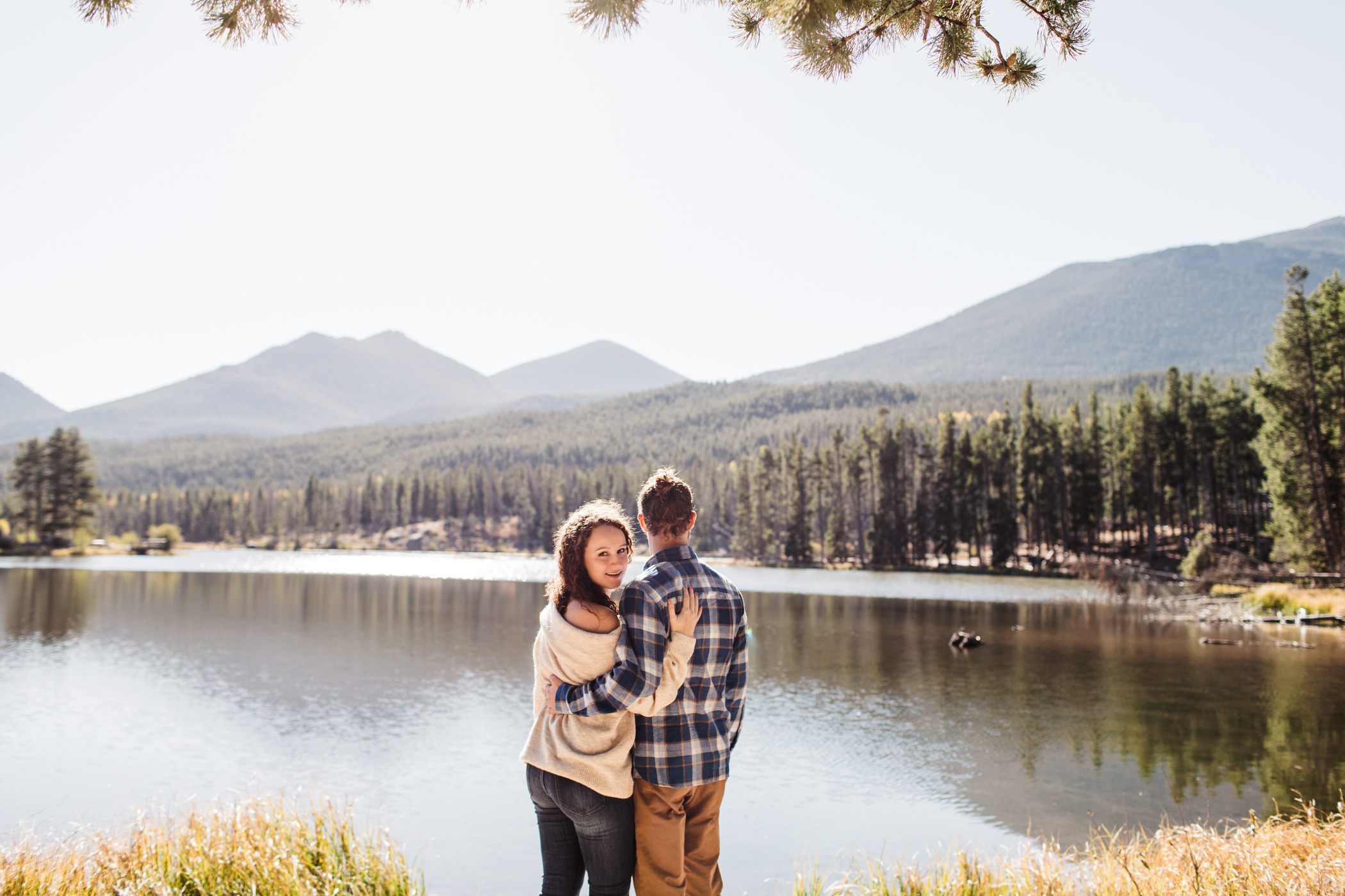 engaged couple looking out at Sprague Lake in Colorado | best Rocky Mountain elopement photographers