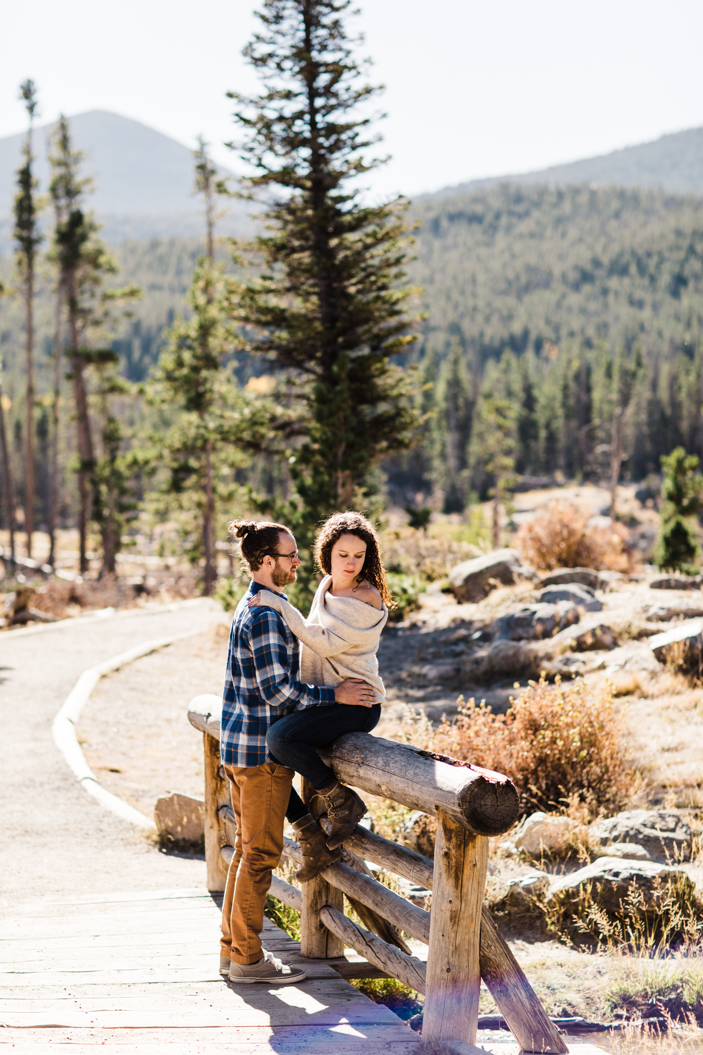 engaged couple hanging out on a bridge by Sprague Lake in Rocky Mountain National Park | Colorado mountain elopement photographers