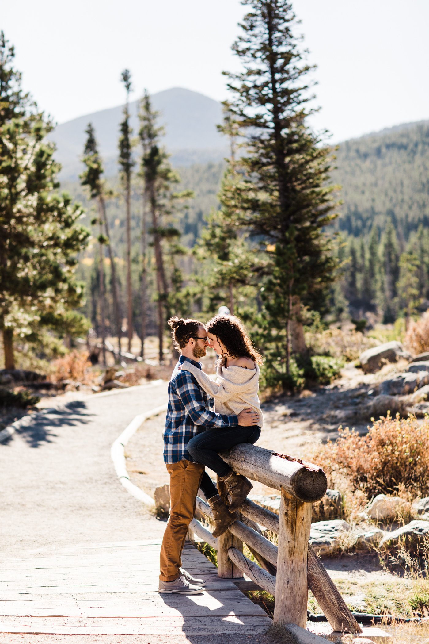 engaged couple snuggling on a bridge by Sprague Lake in Rocky Mountain National Park | Colorado mountain elopement photographers