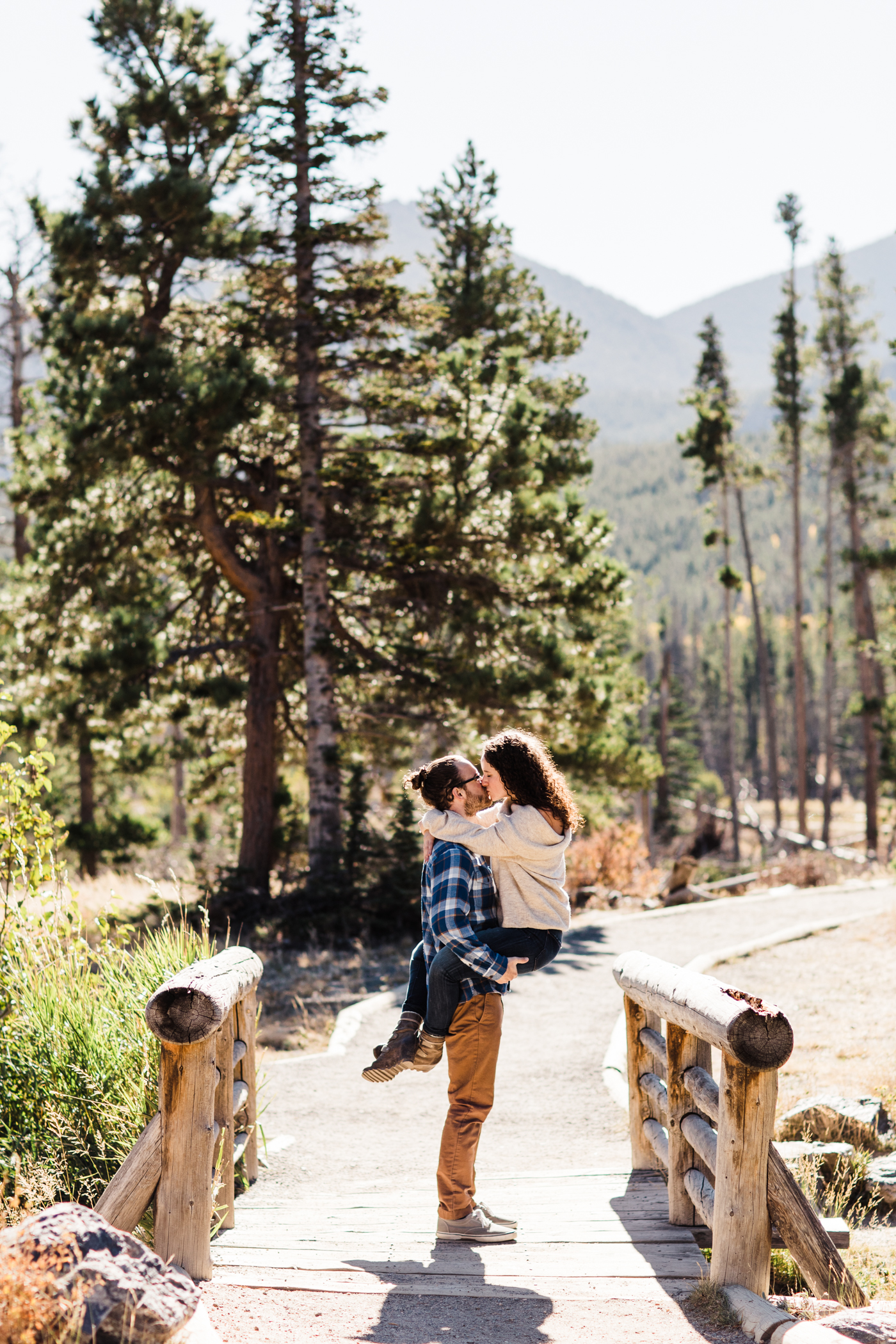engaged couple kissing on a bridge by Sprague Lake in Rocky Mountain National Park | Colorado mountain elopement photographers