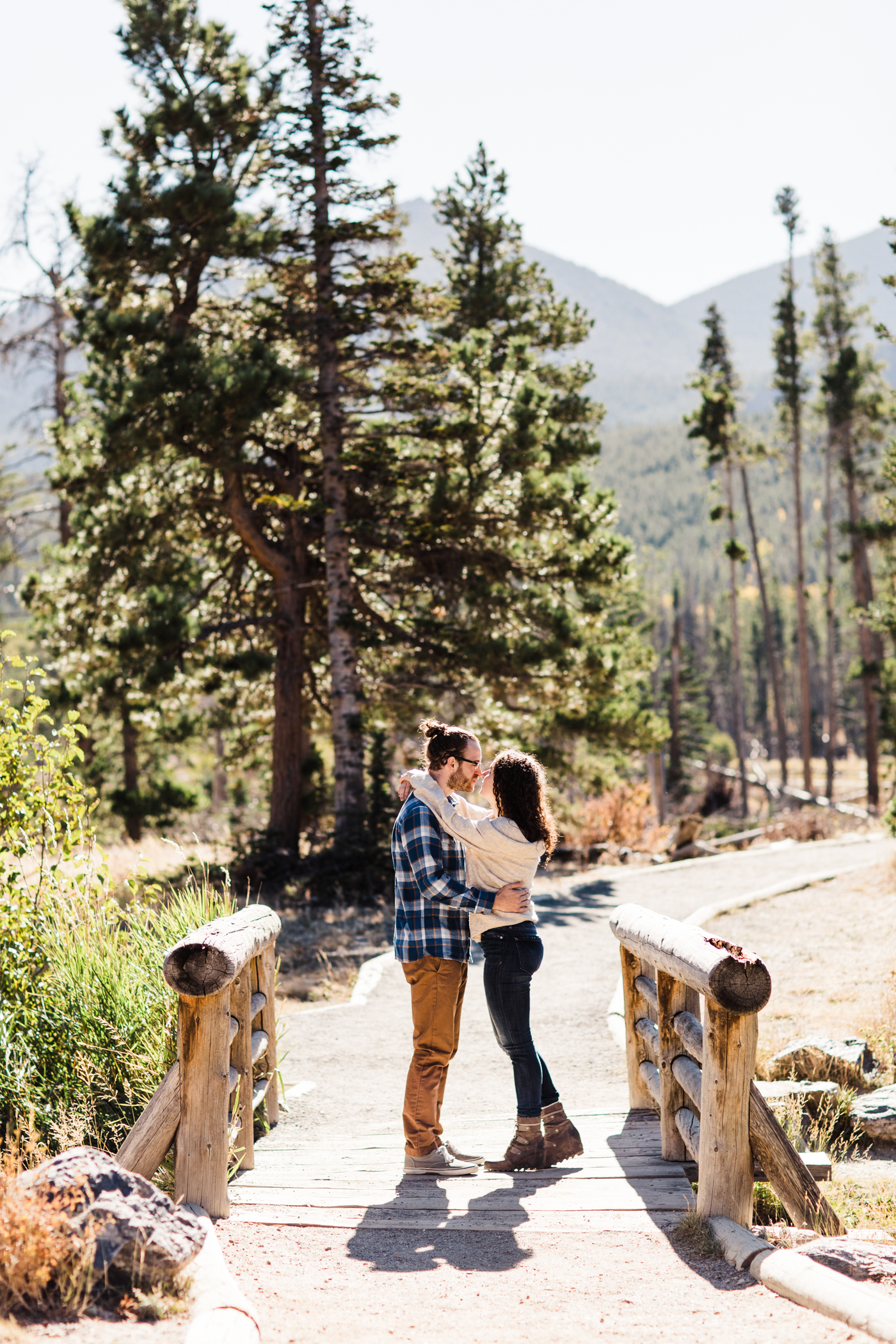 engaged couple kissing on a bridge by Sprague Lake in Rocky Mountain National Park | Colorado elopement photographers
