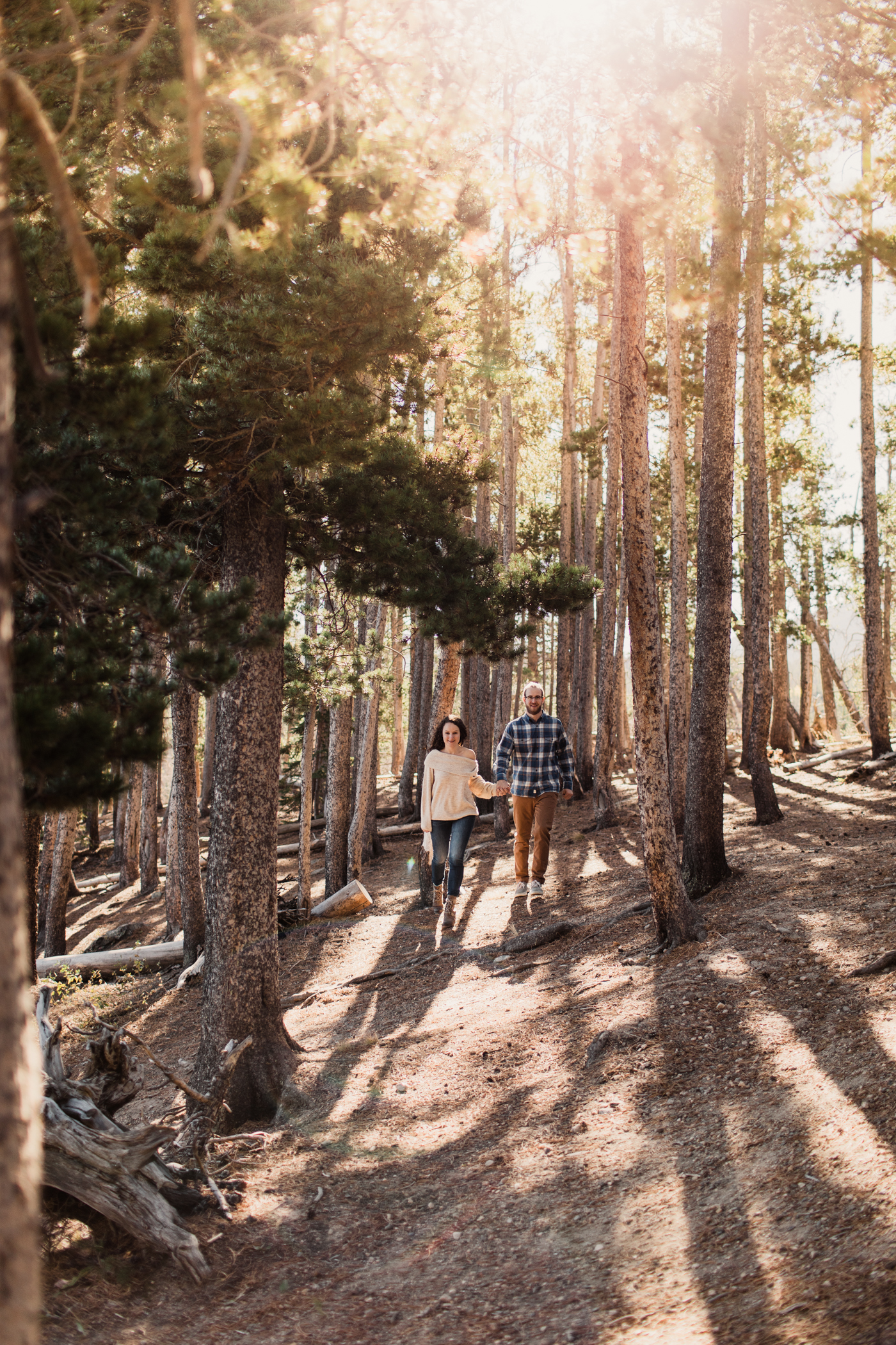 engaged couple running through the woods during their mountain engagement session | best elopement photographers in the Rocky Mountains of Colorado