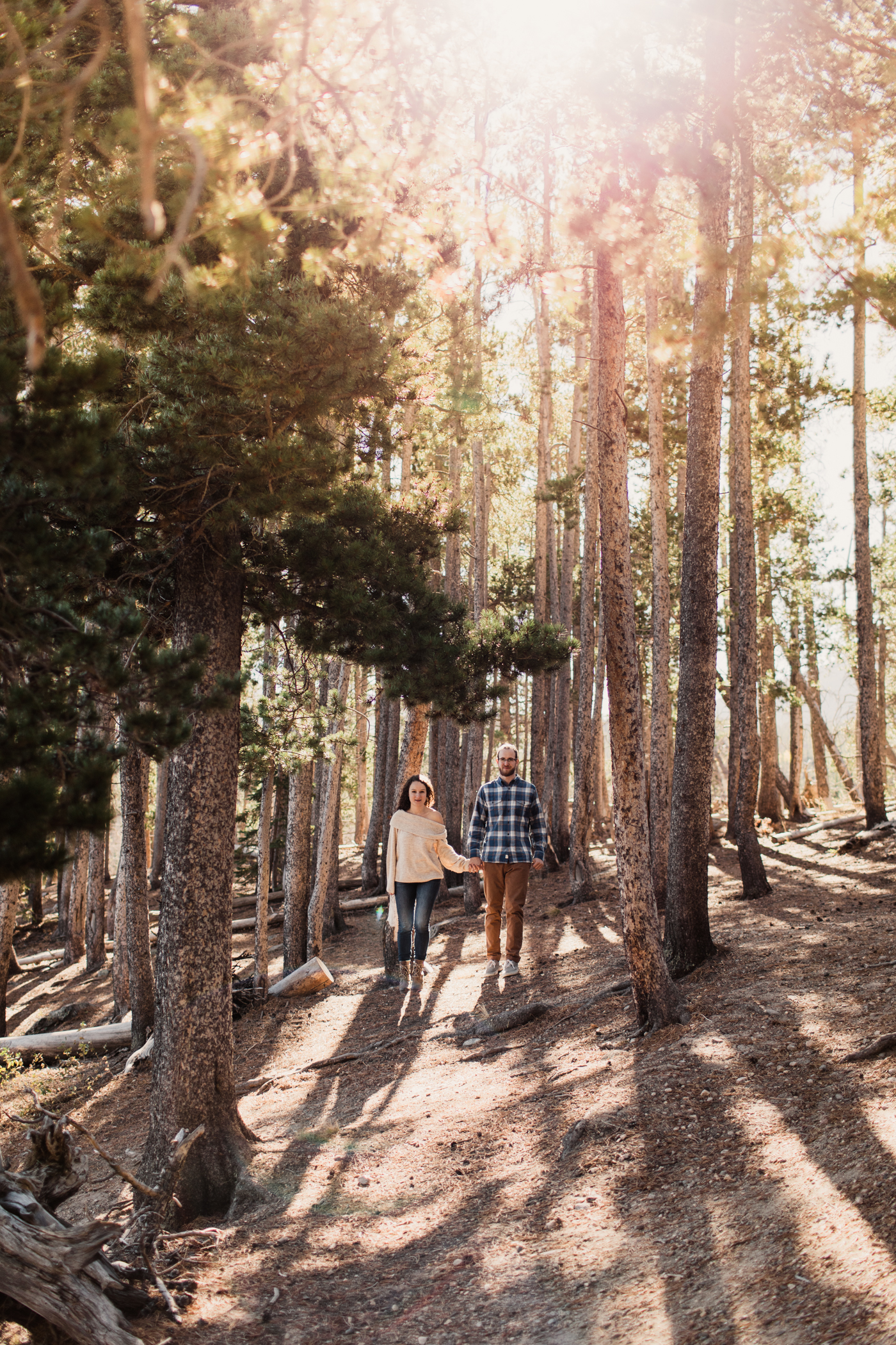 engaged couple running through the woods during their mountain engagement session | best elopement photographers in the Rocky Mountains