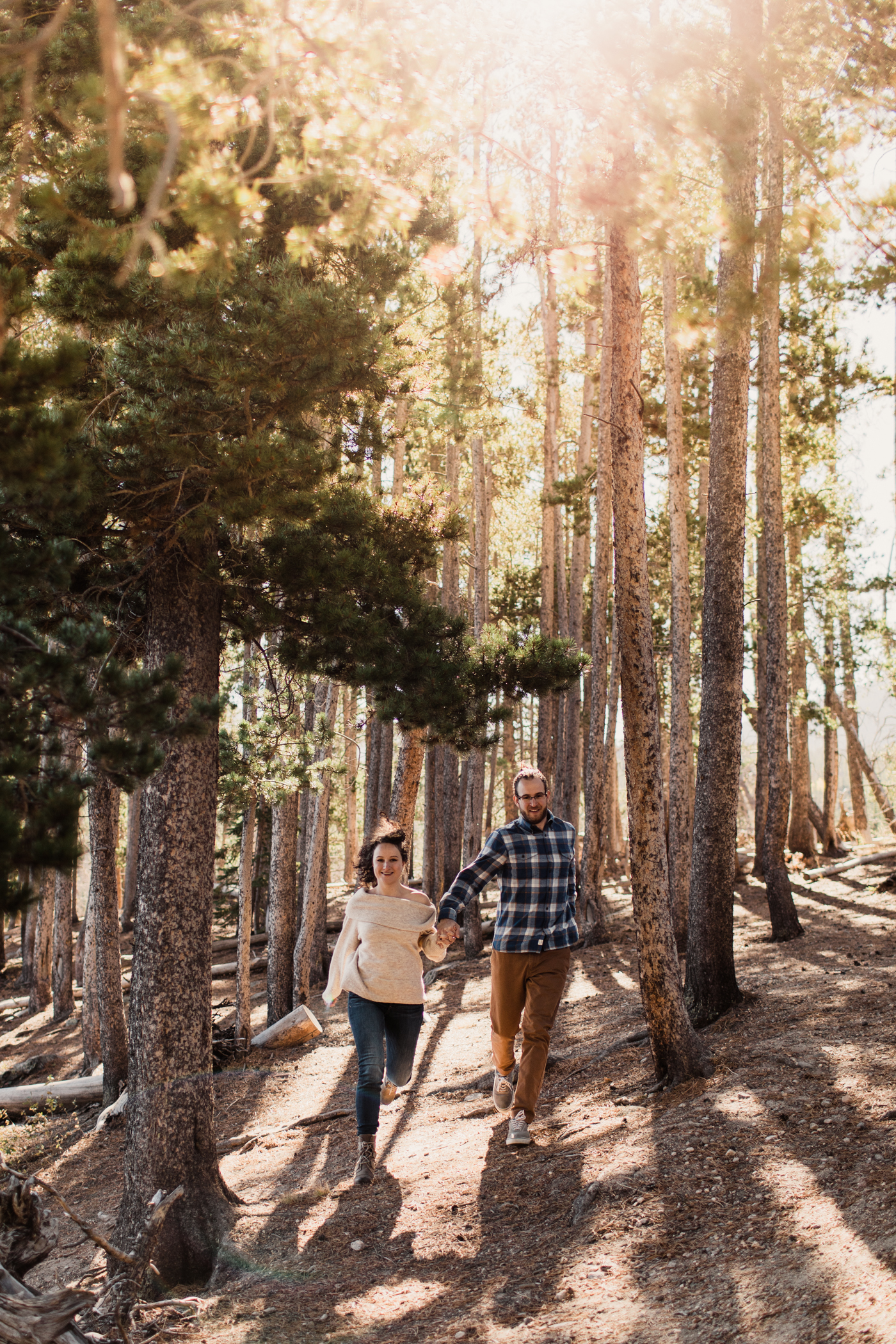engaged couple running through the mountains during their adventurous engagement session | best elopement photographers in the Rocky Mountains