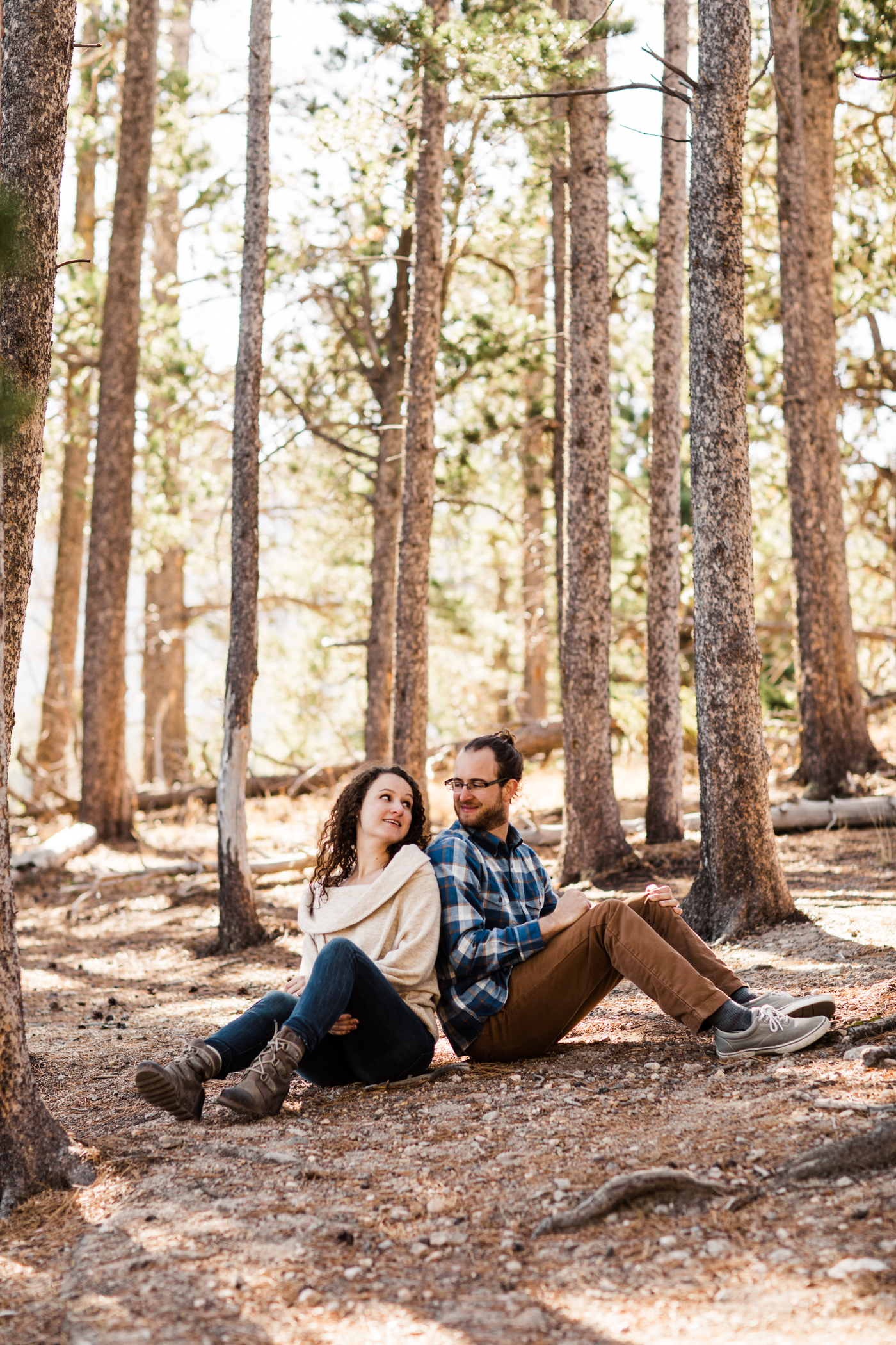 engaged couple sitting back to back in the mountains of Colorado | Rocky Mountain elopement photographers