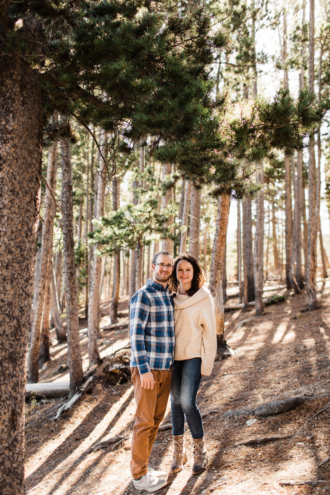 engaged couple smiling at the camera during their adventure session in Rocky Mountain National Park | best elopement photographers in Colorado