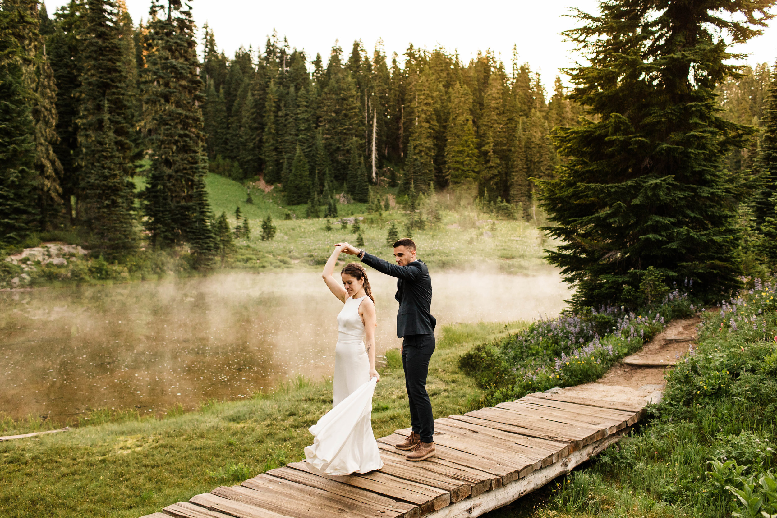 eloping couple dancing by an alpine lake during their Mount Rainier National Park elopement | Washington adventure wedding photographers