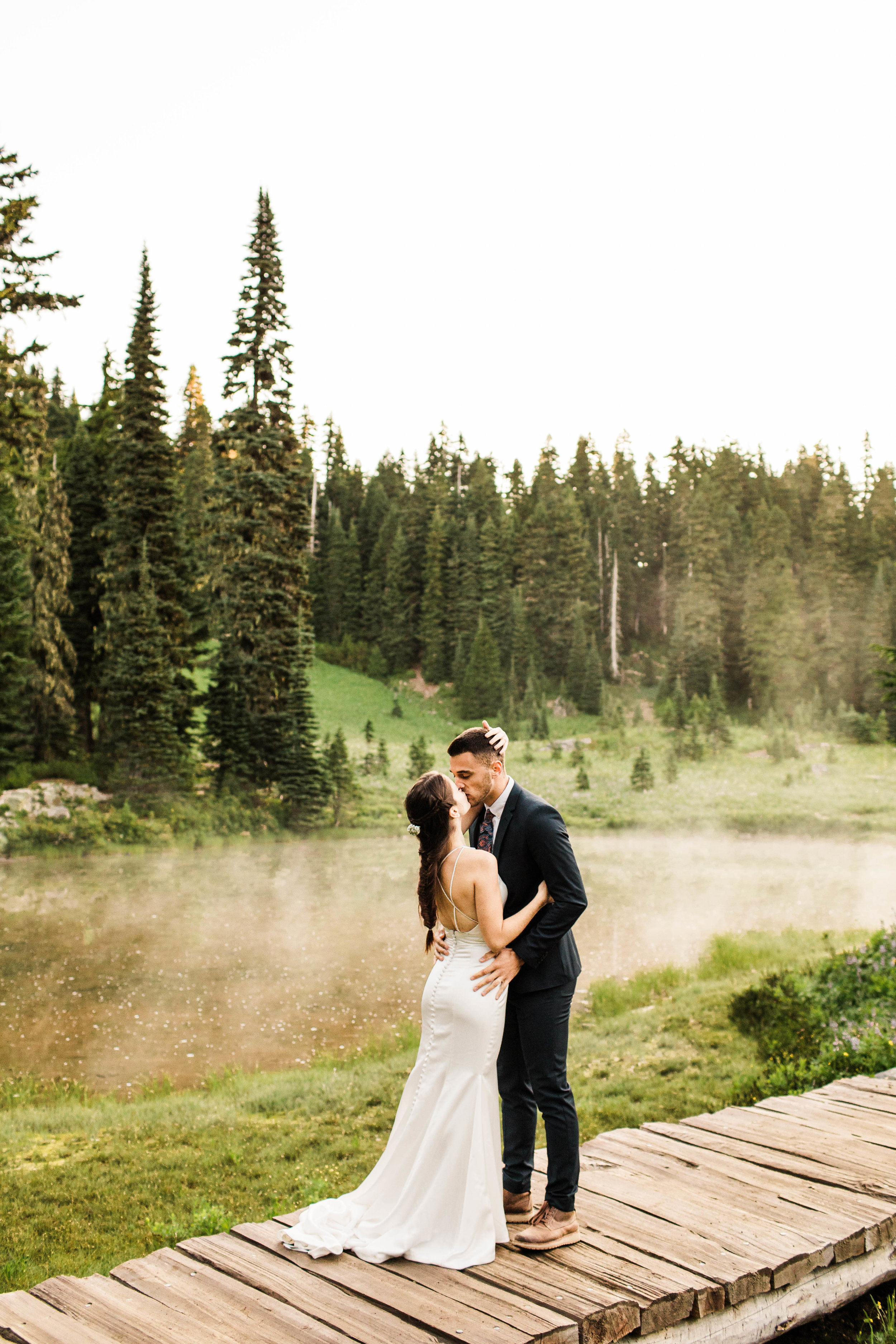 eloping couple kissing by an alpine lake during their Mount Rainier National Park elopement | Seattle Washington adventure wedding photographers