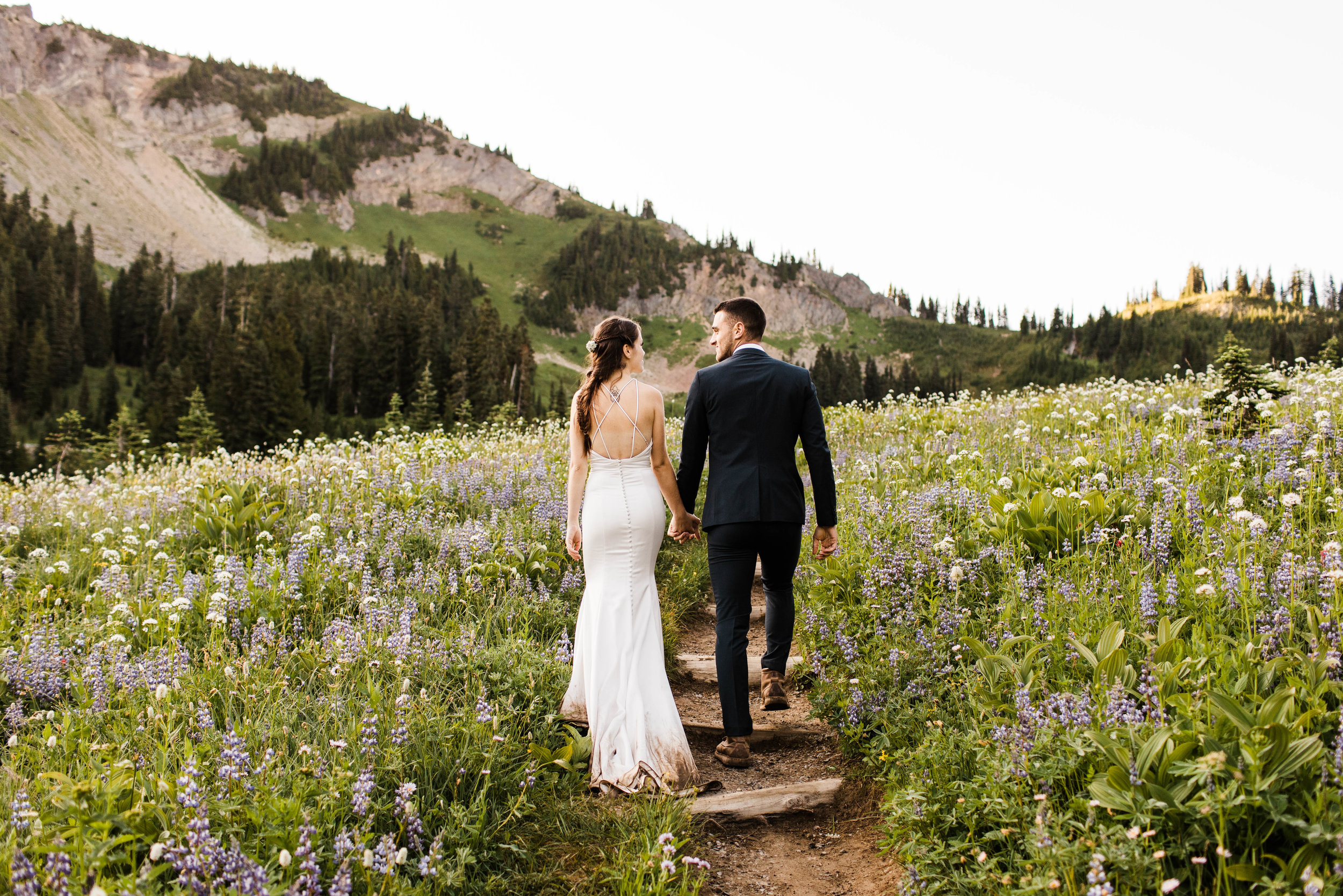 couple hiking for their Mt Rainier National Park elopement | elopement and adventure wedding photographers near Seattle