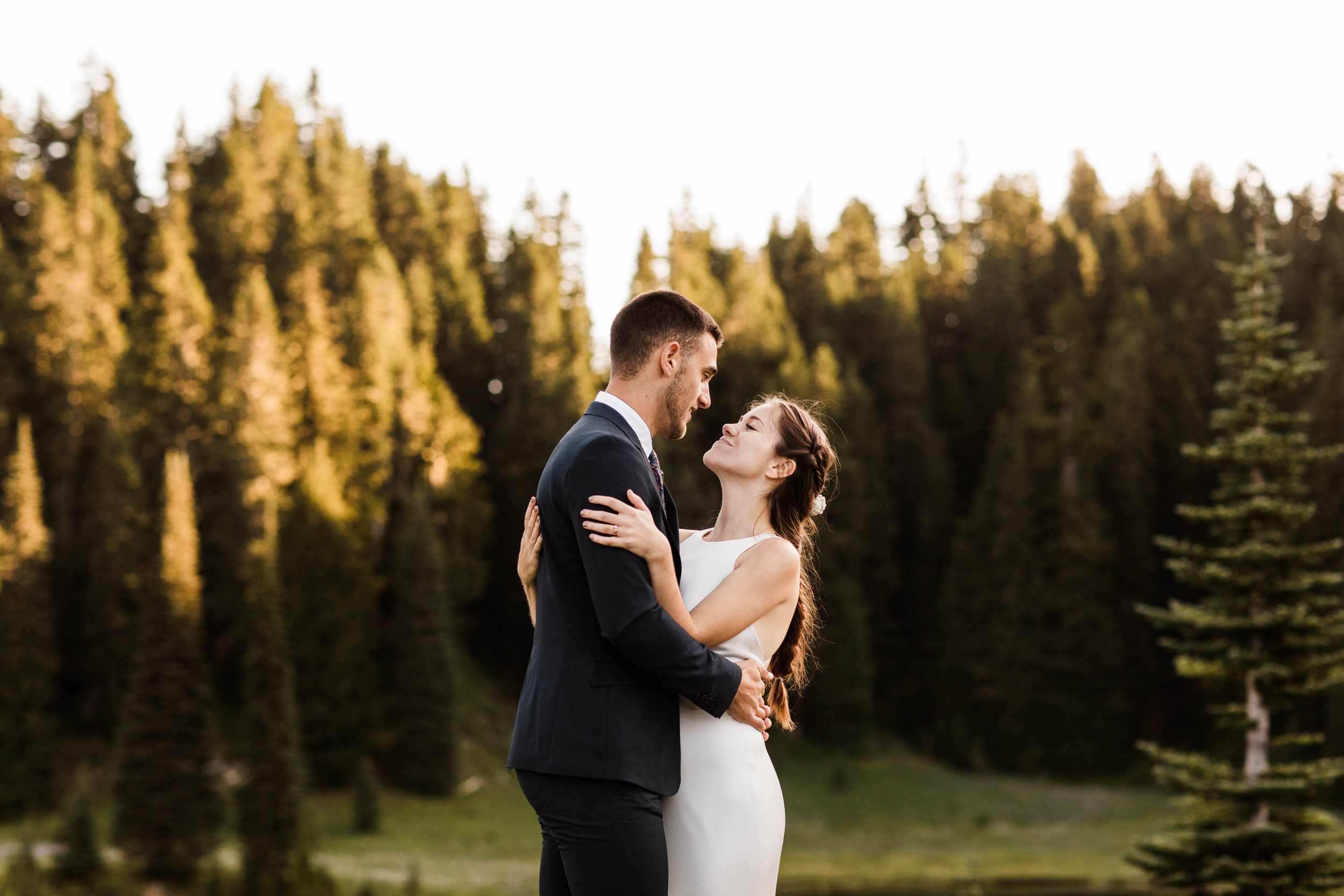 eloping couple watching the sun rise during their Mt Rainier National Park elopement | adventure wedding and elopement photographers in Seattle Washington