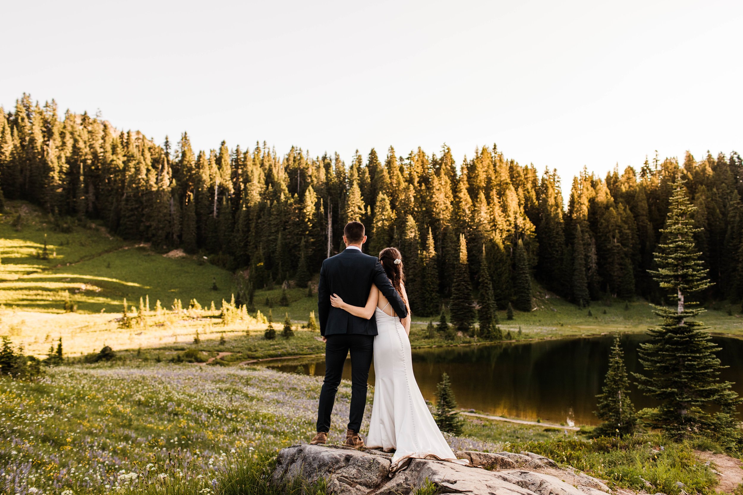eloping couple watching the sun rise during their Mt Rainier National Park elopement | adventure wedding and elopement photographers in Washington state