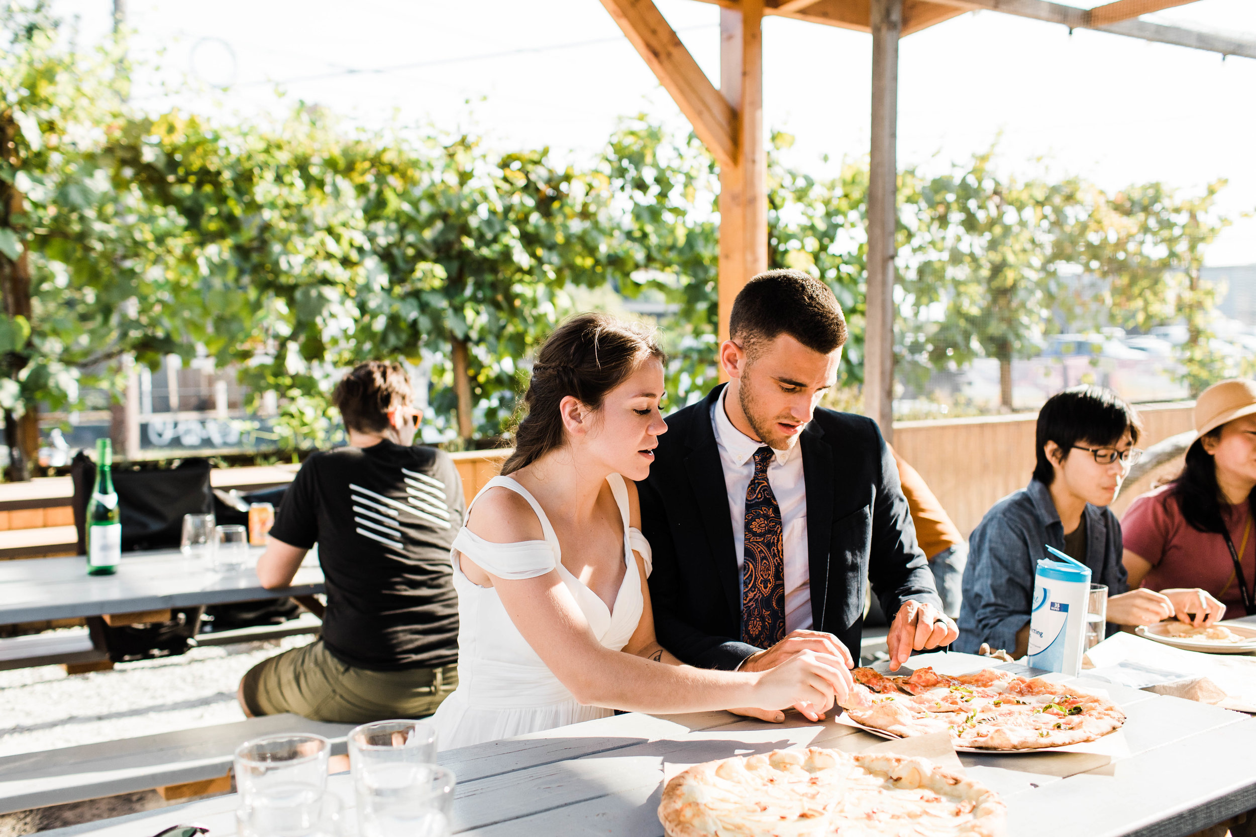 couple eating pizza at Humble Pie in Seattle Washington after their Mt Rainier National Park elopement