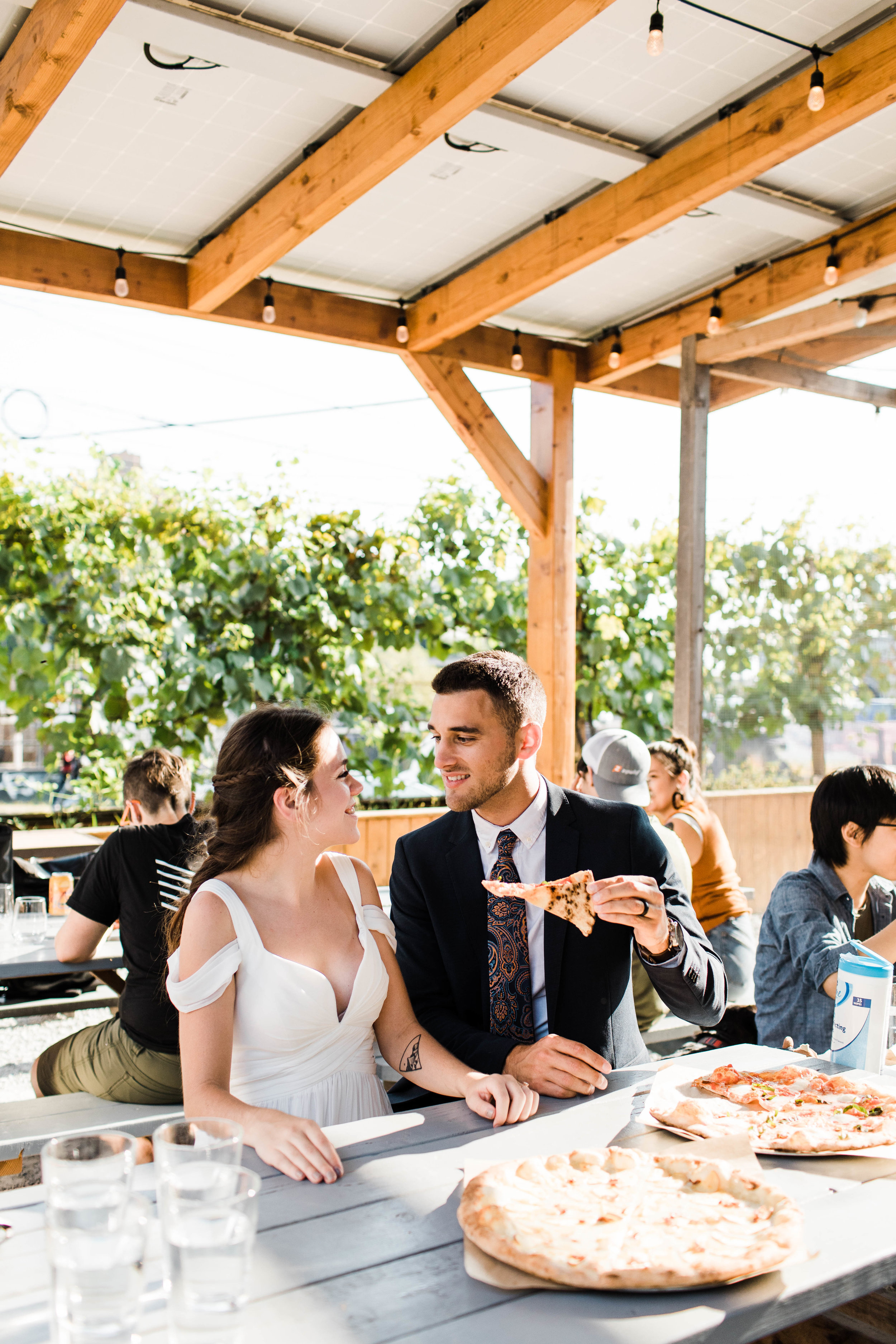 couple feeding each other pizza at Humble Pie in Seattle Washington after their Mt Rainier National Park elopement